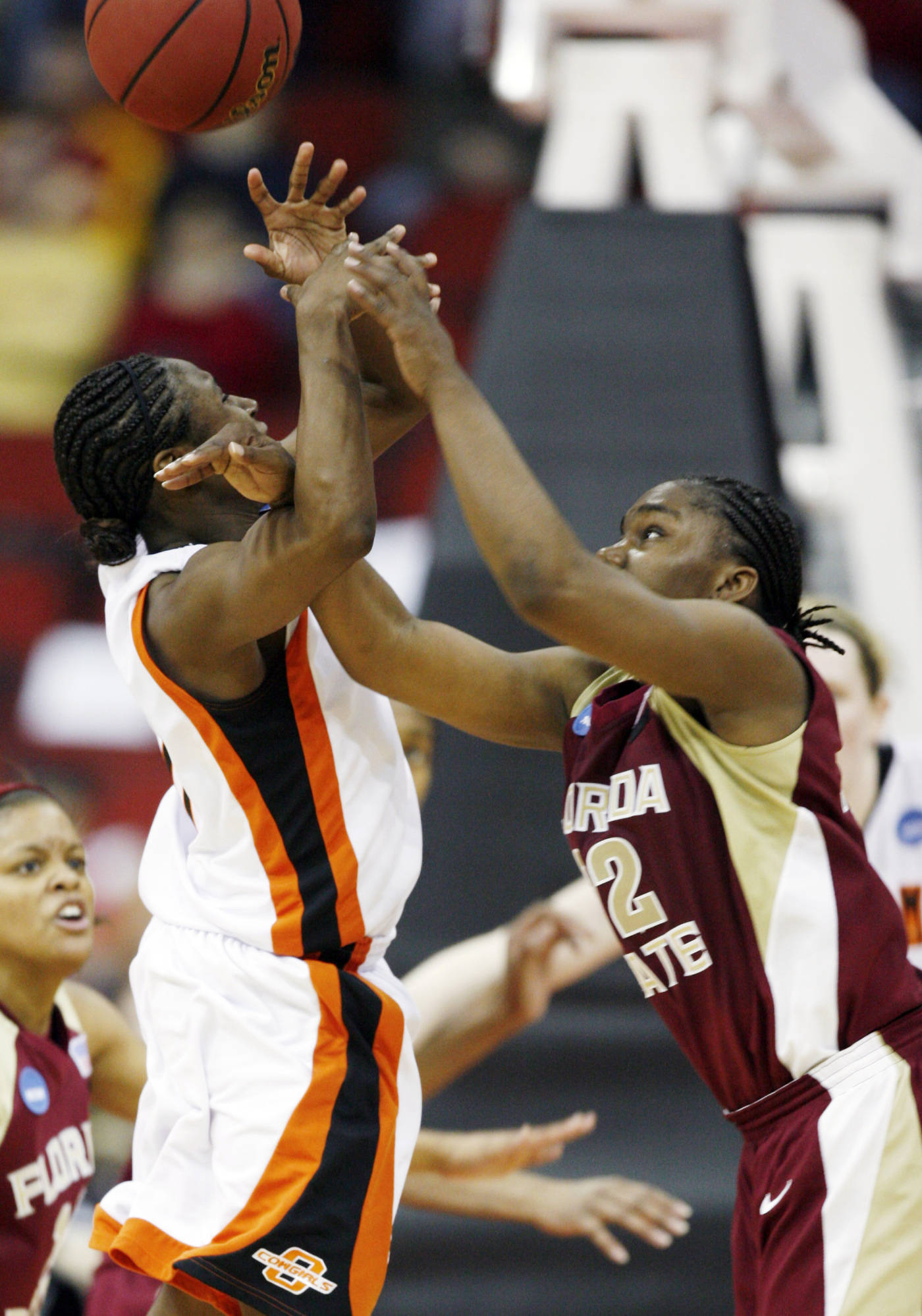 Oklahoma State's Andrea Riley, left, is fouled by Florida State's Shante Williams at the end of an NCAA women's basketball tournament second round game, Monday, March 24, 2008, in Des Moines, Iowa. Riley made a free throw with under one second remaining as Oklahoma State won 73-72 in overtime. (AP Photo/Charlie Neibergall)