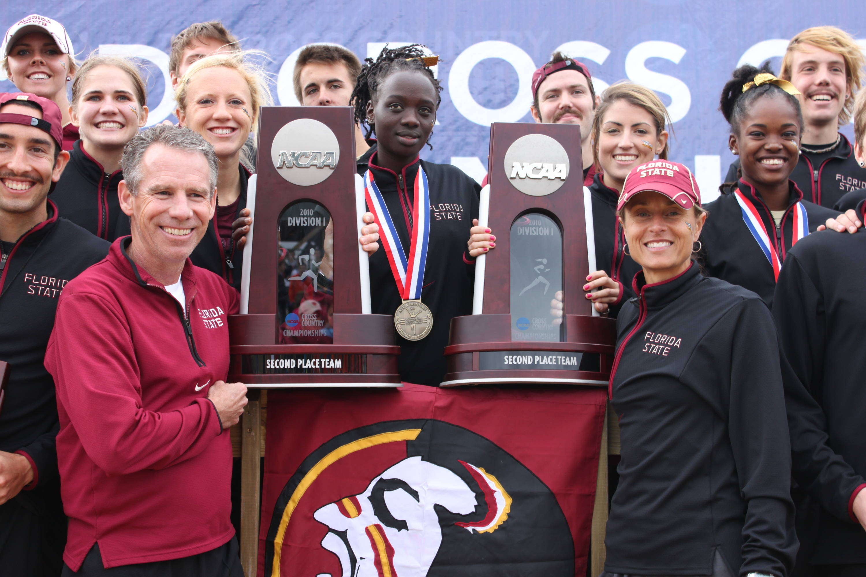 Coaches Bob Braman and Karen Harvey beam with the latest hardware additions to the cross country trophy case.