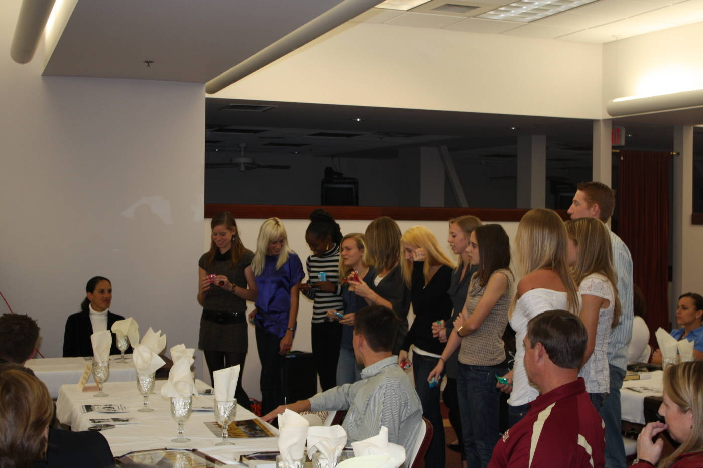 The women's cross country team being honored by head coach Karen Harvey