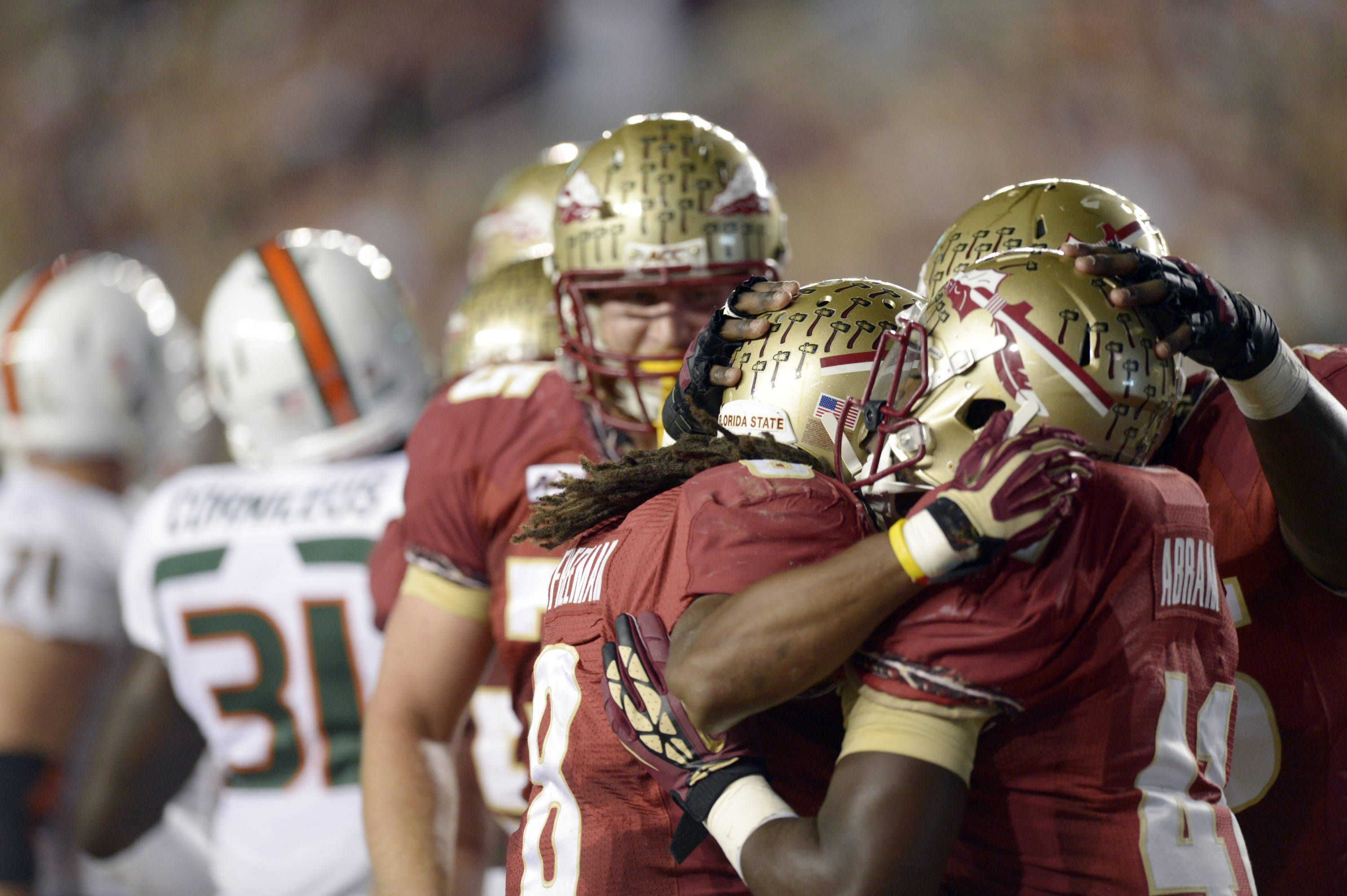 Florida State Seminoles running back Devonta Freeman (8) celebrates his touchdown with fullback Chad Abram (41) and offensive linesman Cameron Erving (75) against the Miami Hurricanes during the first quarter at Doak Campbell Stadium. Mandatory Credit: John David Mercer-USA TODAY Sports