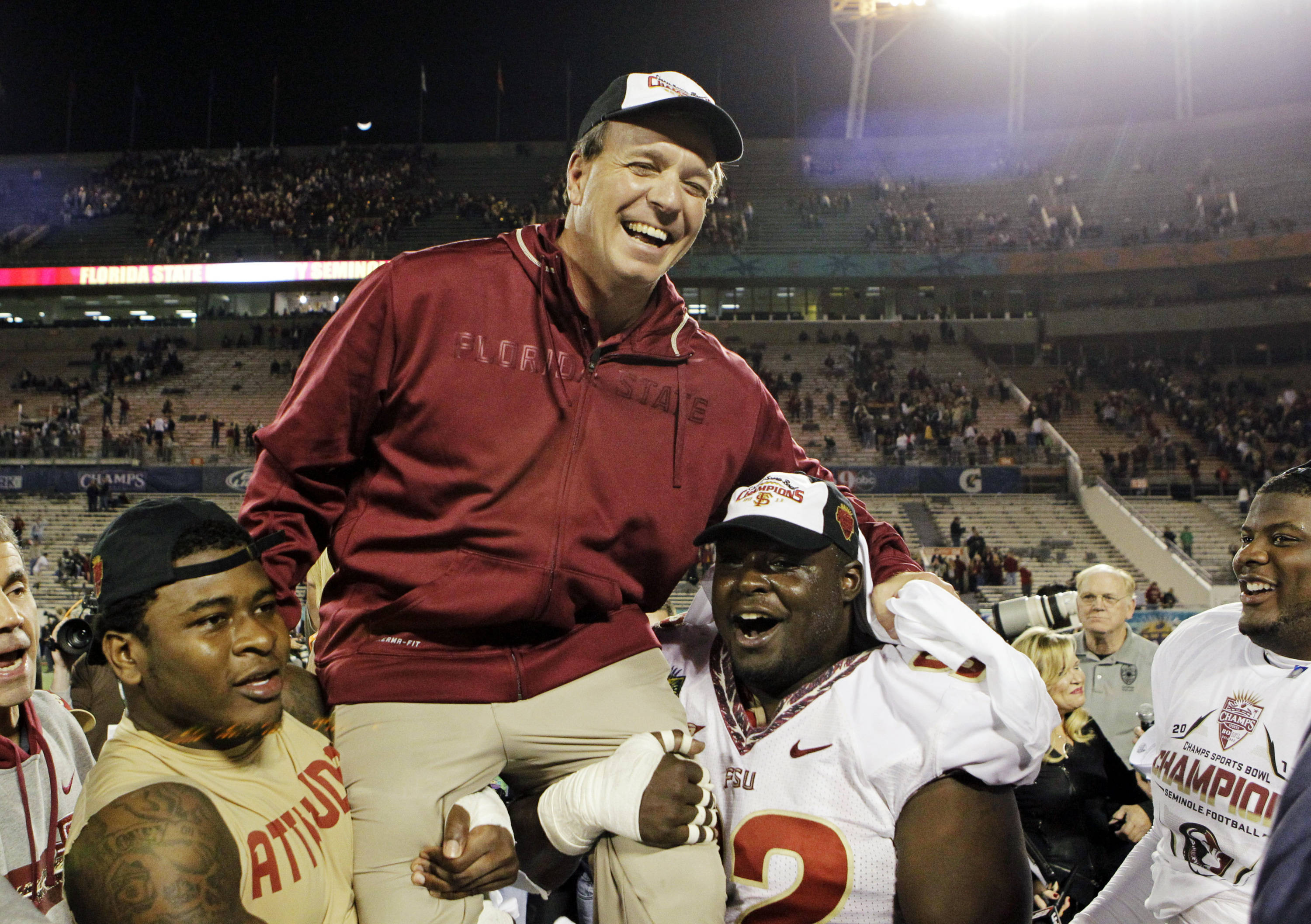 Florida State players carry head coach Jimbo Fisher off the field after they defeated Notre Dame 18-14 in the Champs Sports Bowl. (AP Photo/John Raoux)