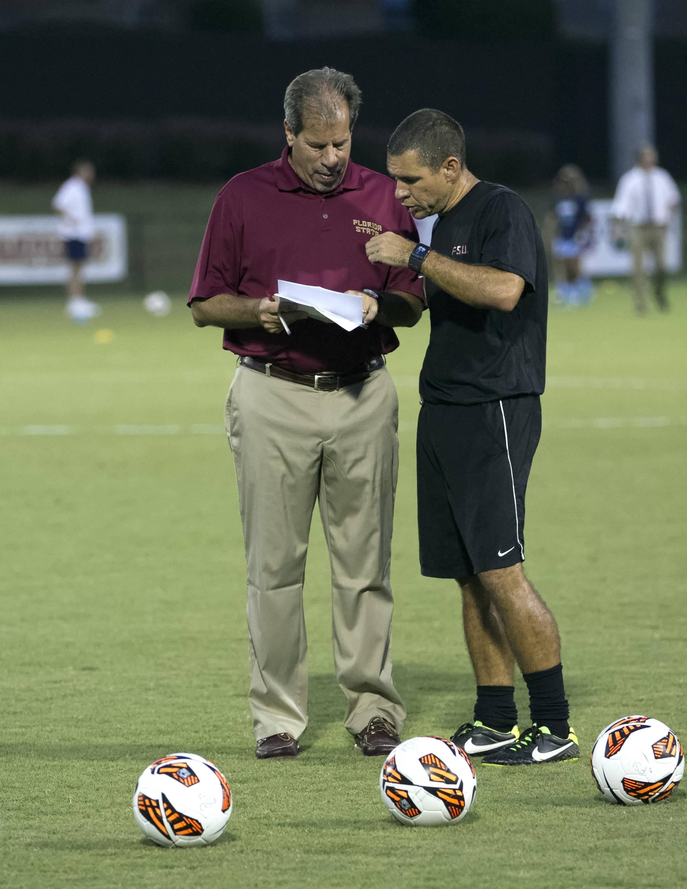 Head Coach Mark Krikorian talking stragegy with Assistant Coach Mike Bristol, FSU vs North Carolina,  9-18-13, (Photo by Steve Musco)