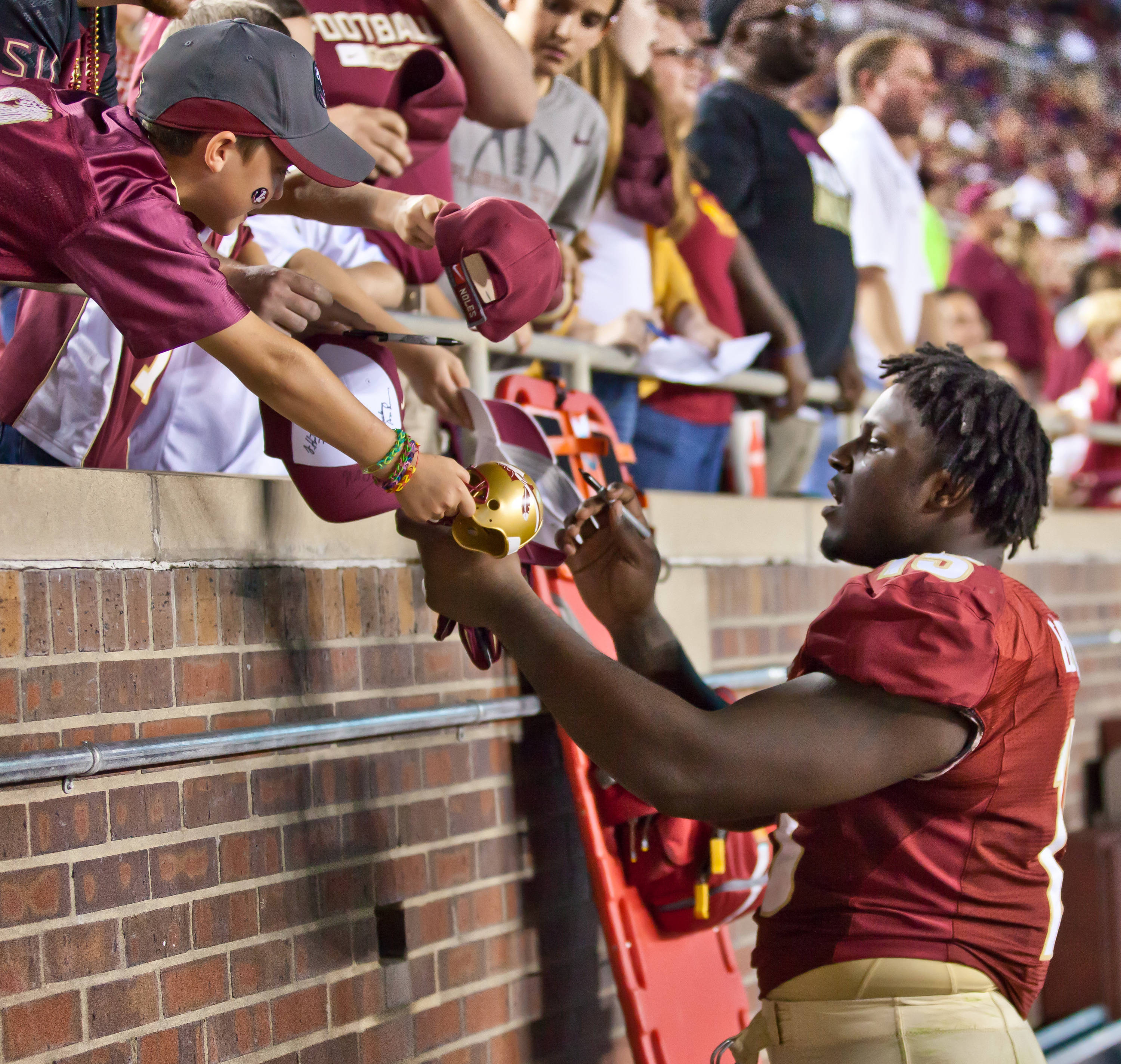 Jr. Edwards Mario (15) signs autographs for young fans.
