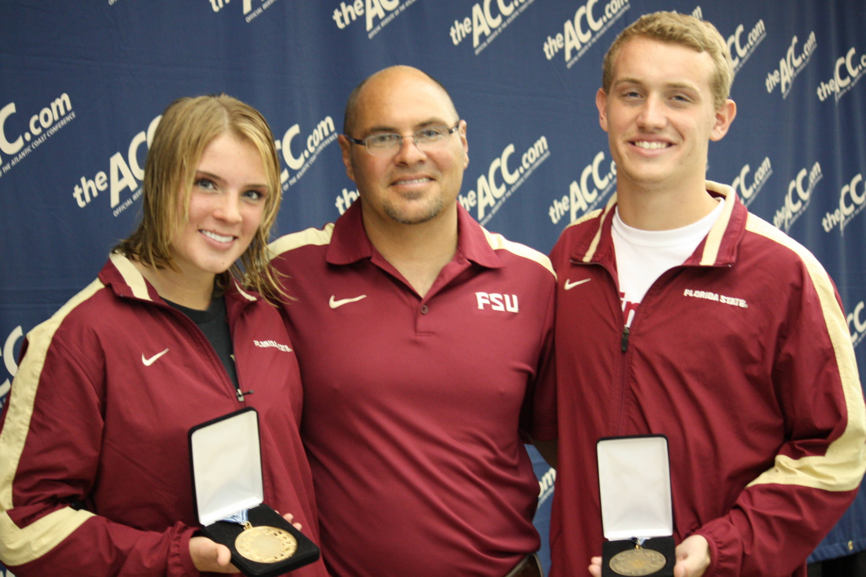Head Coach Pat Jeffrey smiles with his two podium divers on the final night of competition.