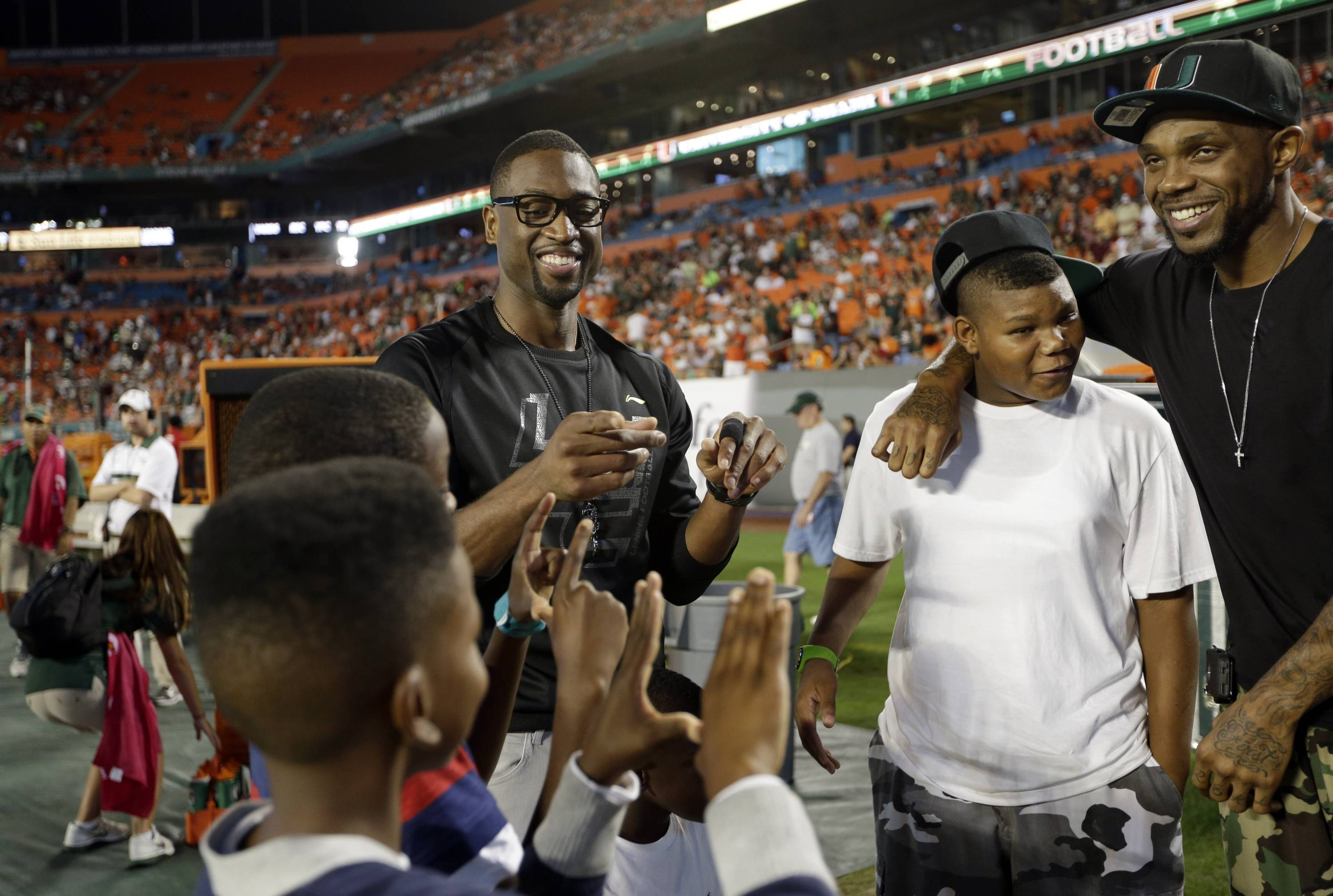 Miami Heat's Dwyane Wade, center, and Udonis Haslem, right, stand on the sideline before an NCAA college football game against Florida State, Saturday, Oct. 20, 2012, in Miami. (AP Photo/Lynne Sladky)