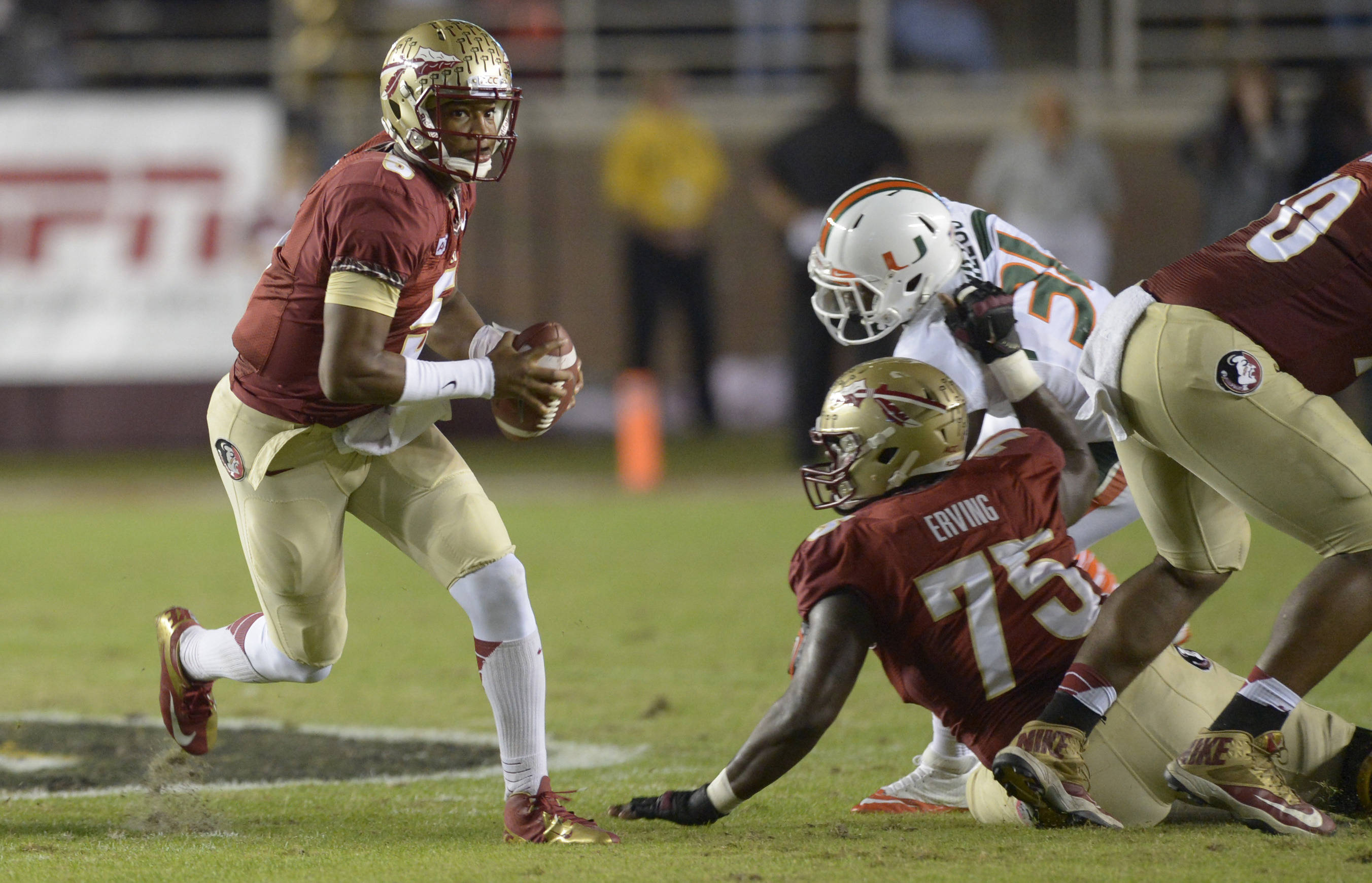Florida State Seminoles quarterback Jameis Winston (5) scrambles out of the pocket against the Miami Hurricanes during the first quarter at Doak Campbell Stadium. Mandatory Credit: John David Mercer-USA TODAY Sports