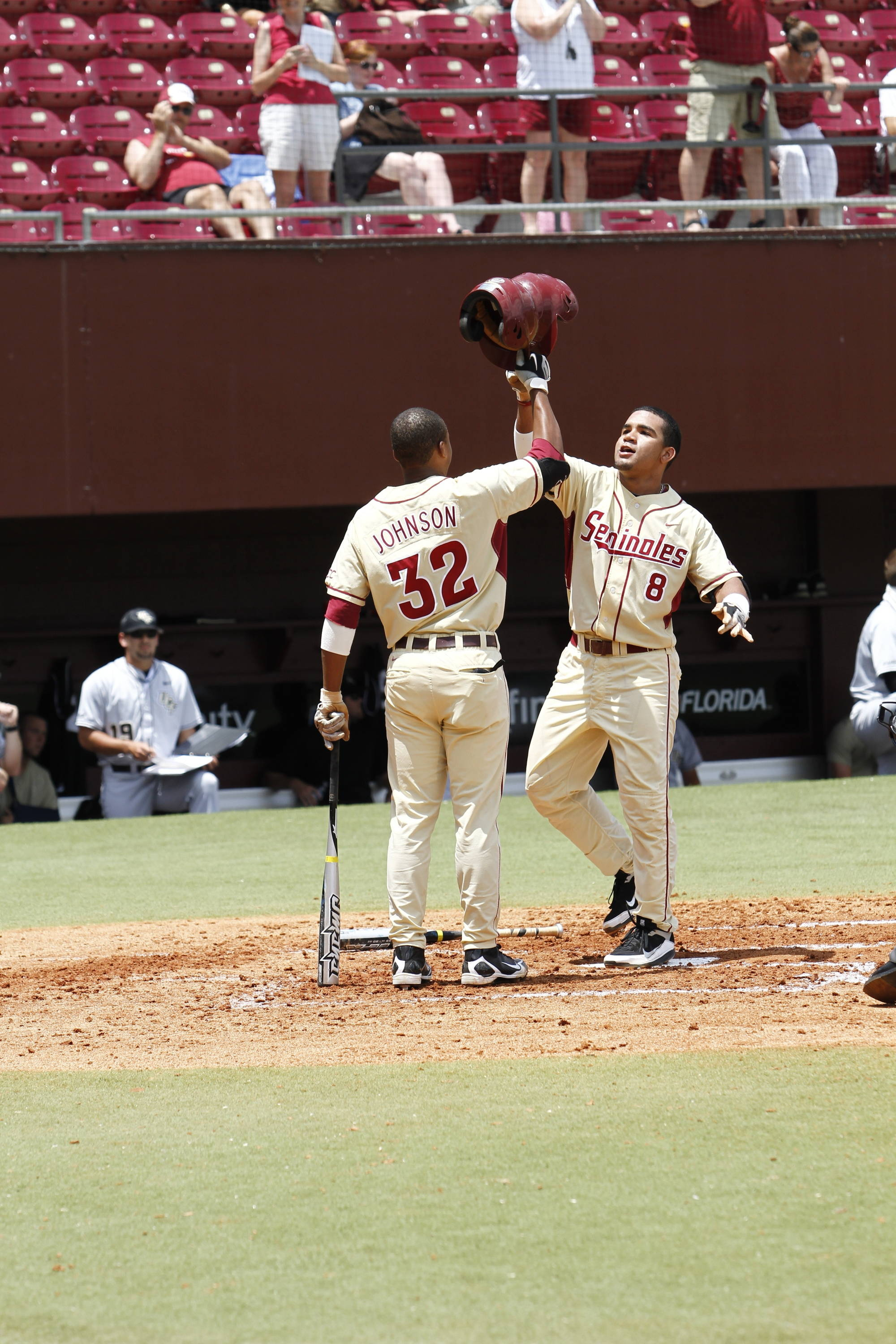 "Devon Travis (8) sharing ""high helmets  following his home run by Sherman Johnson (32)"