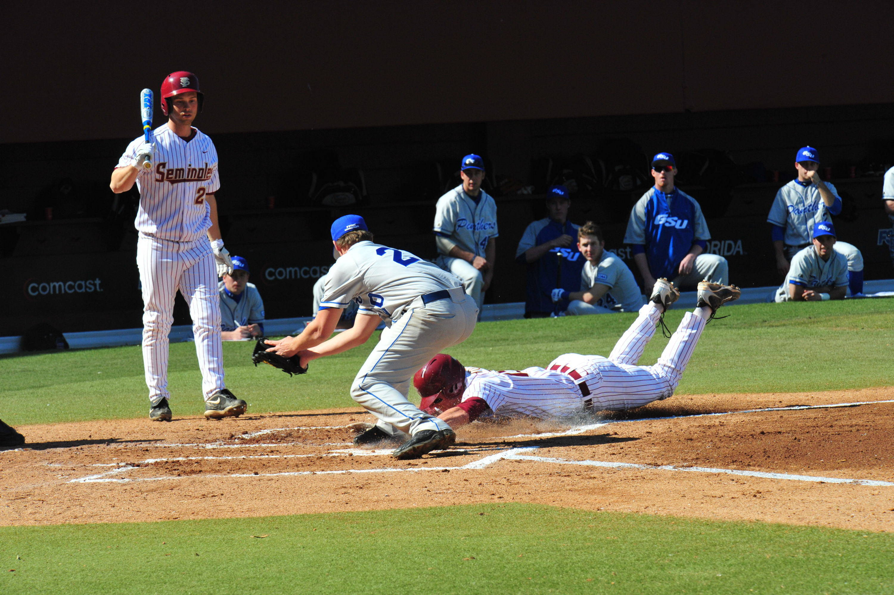 Tyler Holt slides in safely at home following a Georgia State passed ball.
