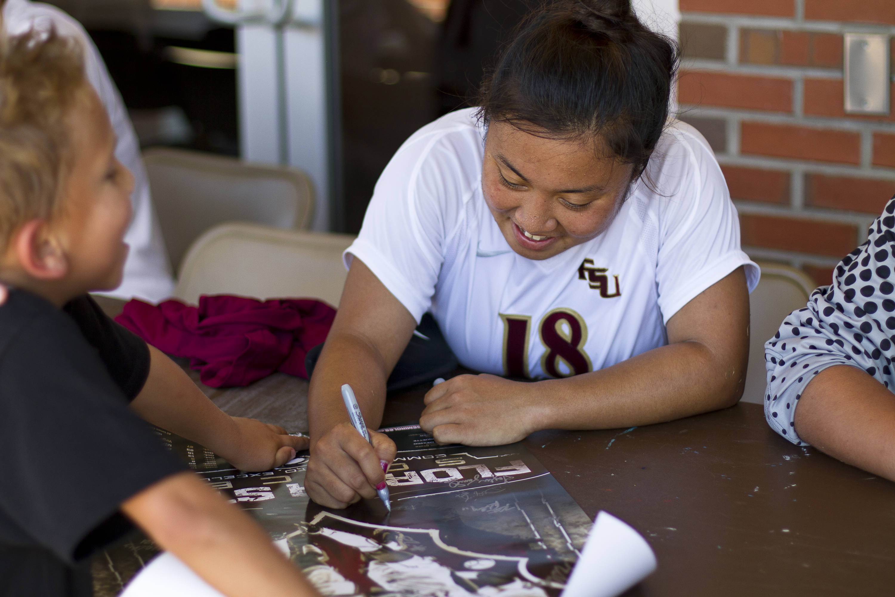 Hikaru Murakami (18) autographs a poster for a young fan after the game against North Florida.