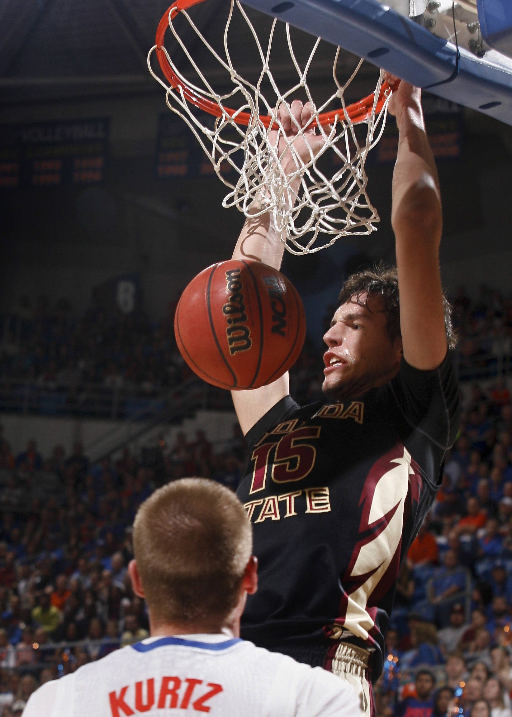 Nov 29, 2013; Gainesville, FL, USA; Seminoles center Boris Bojanovsky (15) dunks as Florida Gators forward Jacob Kurtz watches. Phil Sears-USA TODAY Sports