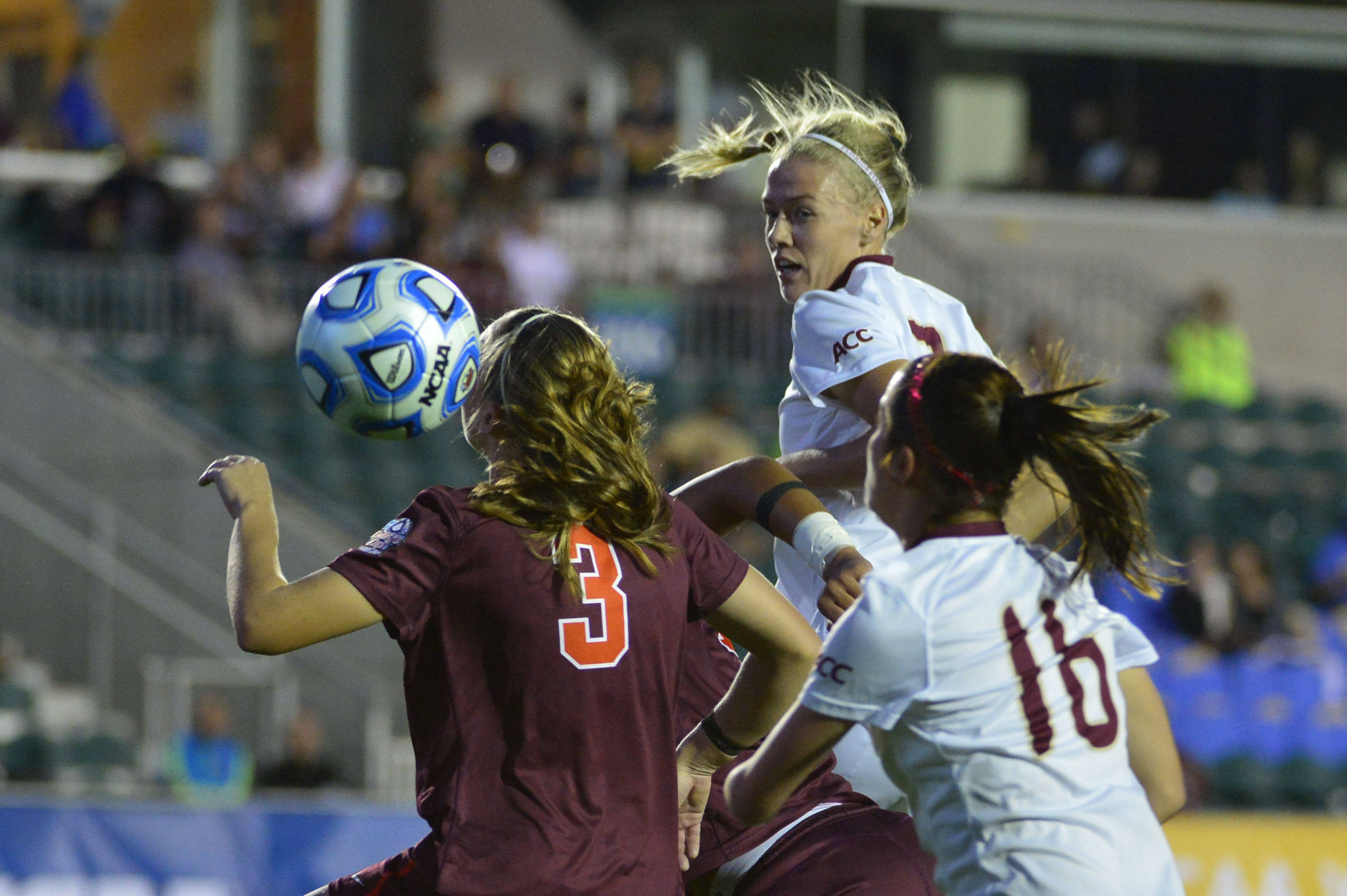 Dec 6, 2013; Cary, NC, USA; Florida State Seminoles midfielder Dagny Brynjarsdottir (7) heads the ball as midfielder Carson Pickett (16) is in the foreground and Virginia Tech Hokies midfielder Katie Yensen (3) defends in the first half at WakeMed Soccer Park. Mandatory Credit: Bob Donnan-USA TODAY Sports