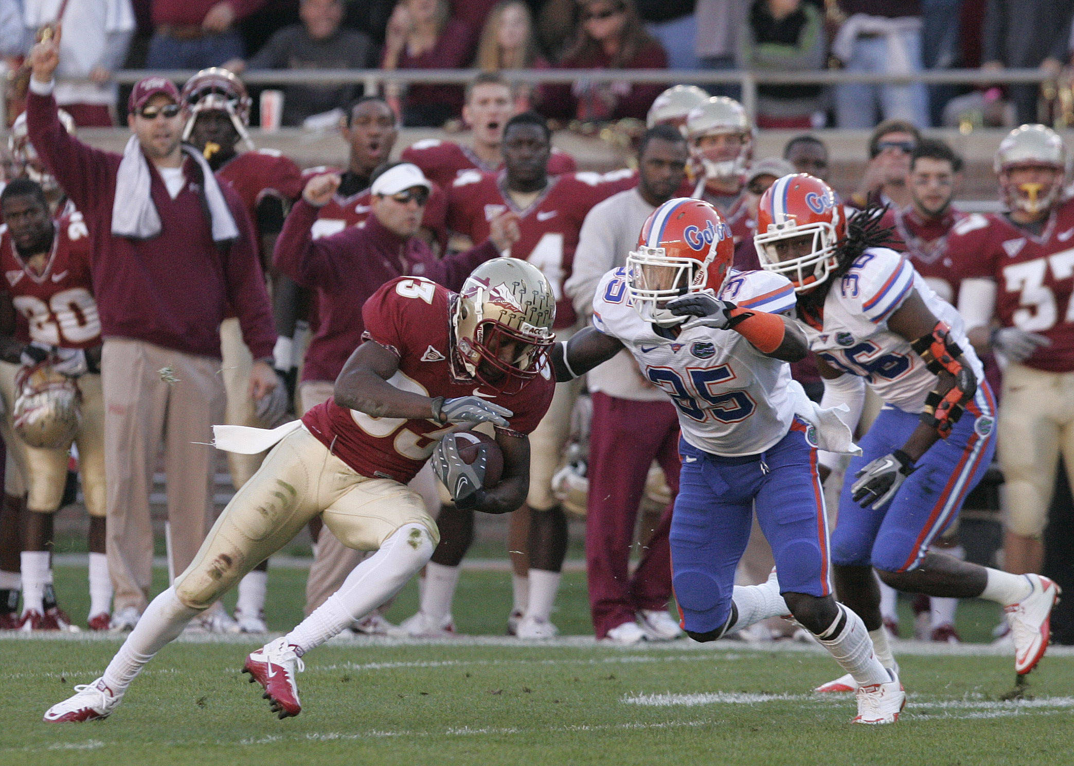 Florida State's Bert Reed turns upfield after making a reception as Florida's  Ahmad Black, center, and Moses Jenkins move in for the tackle in the first quarter of an NCAA college football game Saturday, Nov. 27, 2010, in Tallahassee, Fla.(AP Photo/Steve Cannon)