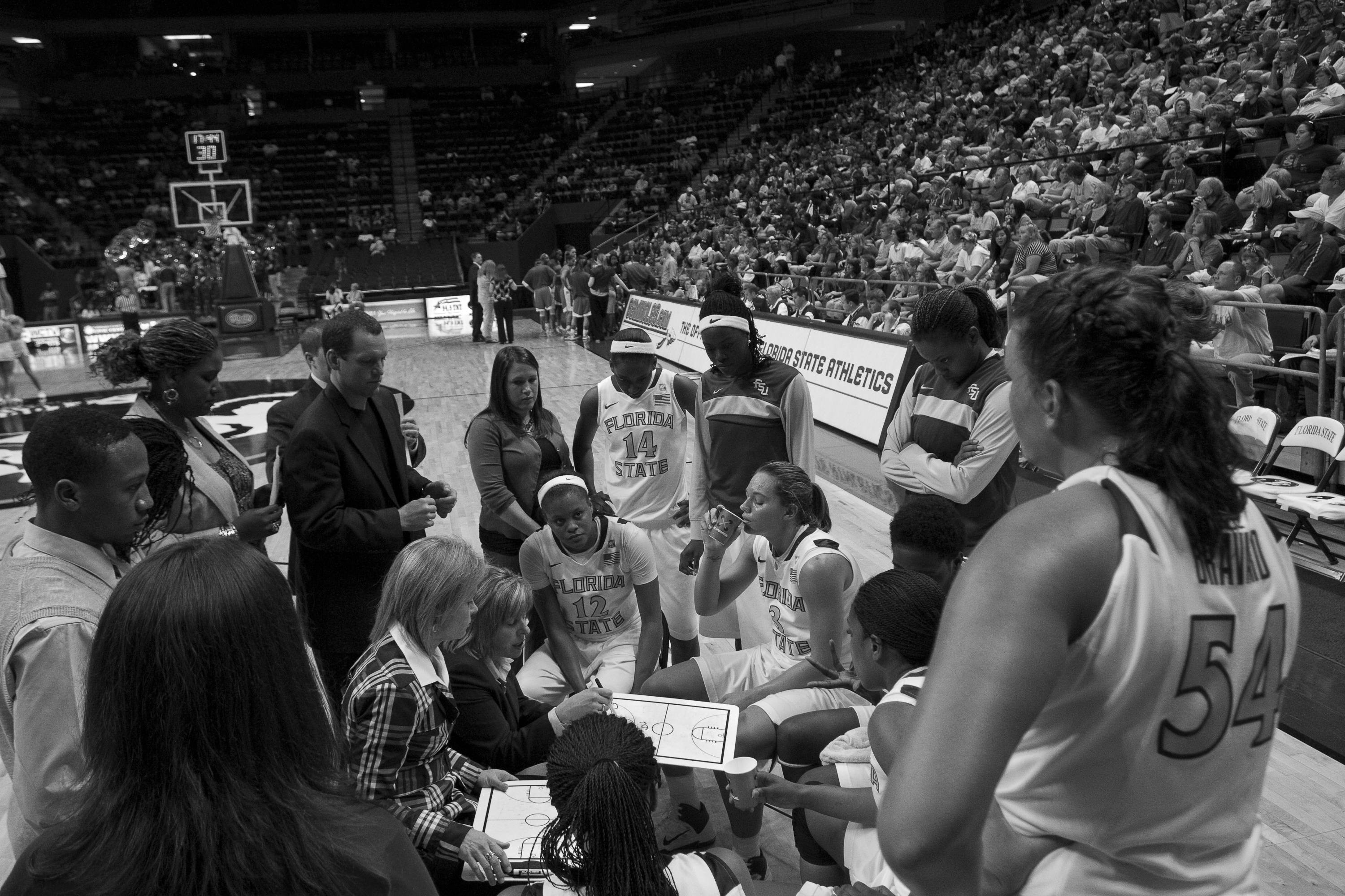 Coach Sue Semrau talks with the team during a time-out
