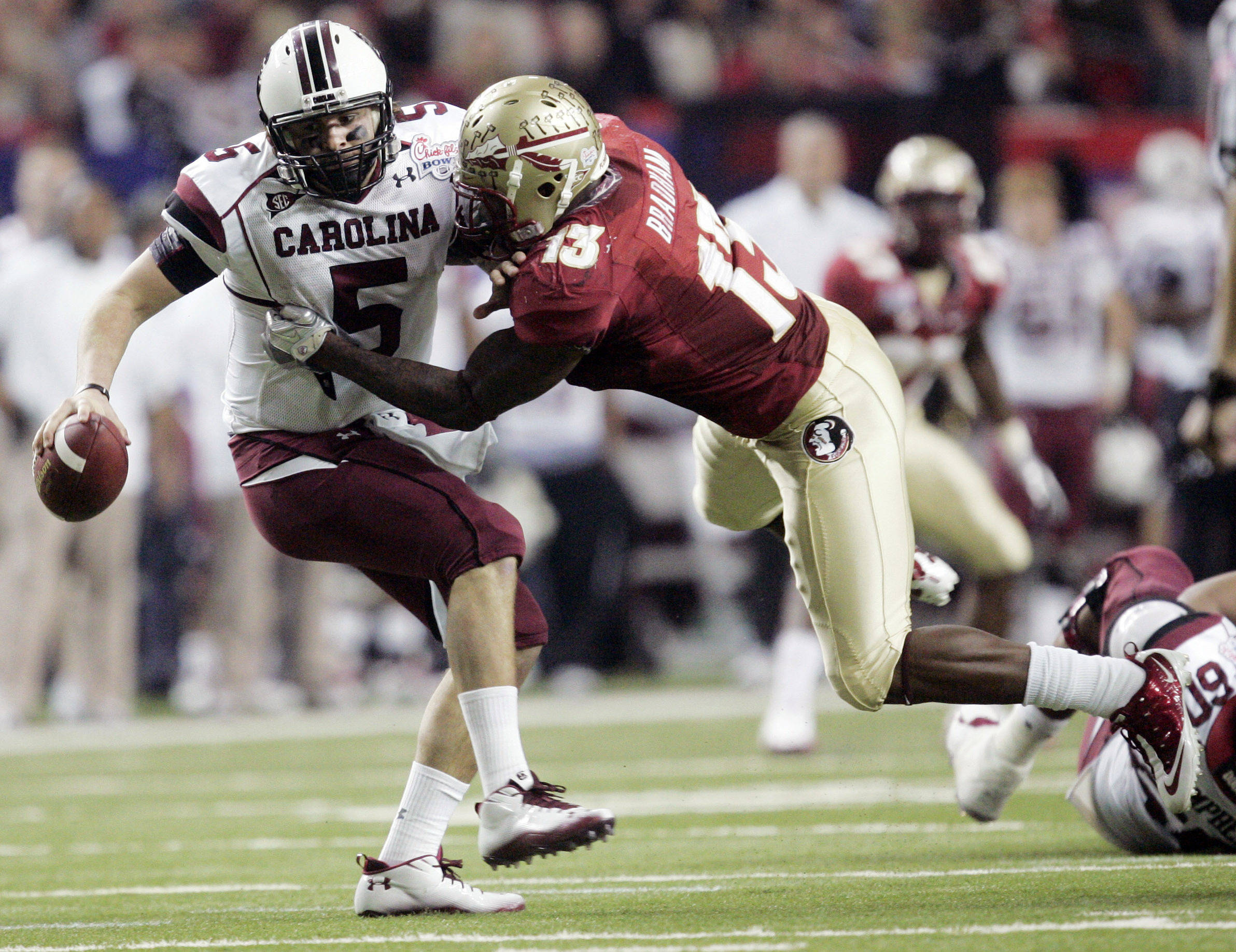 South Carolina quarterback Stephen Garcia (5) is sacked by Florida State linebacker Nigel Bradham (13) in the second quarter of the Chick-fil-A Bowl NCAA college football game on Friday, Dec. 31, 2010, in Atlanta. (AP Photo/John Amis)