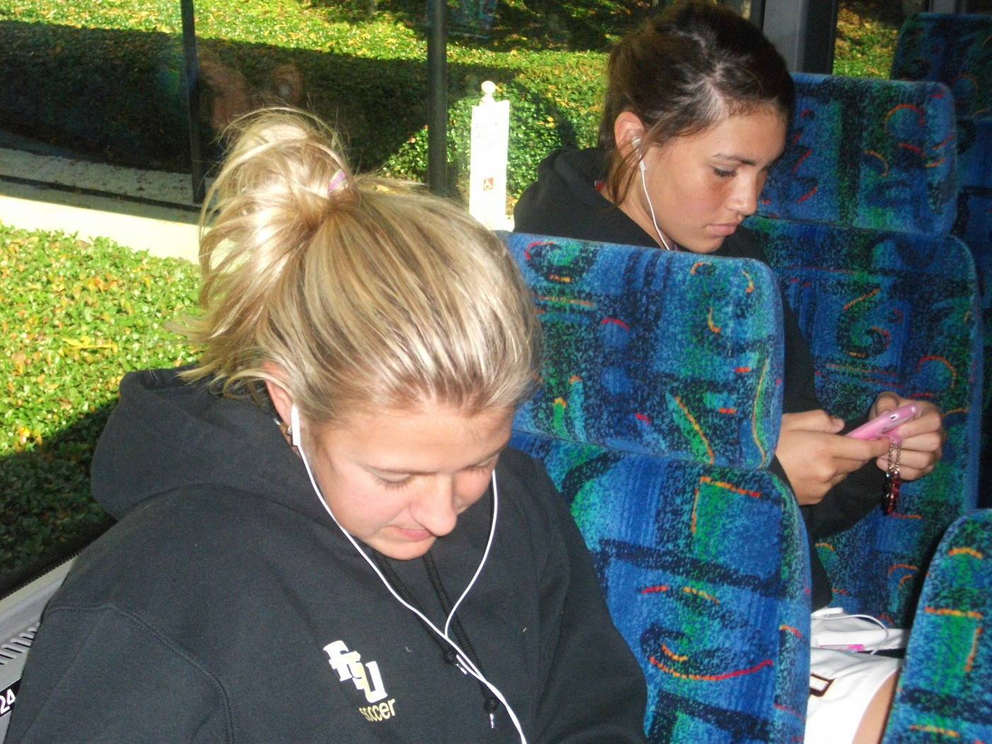 Breezy Hupp and Tiana Brockway listen to some music on the bus ride over to WakeMed Park.