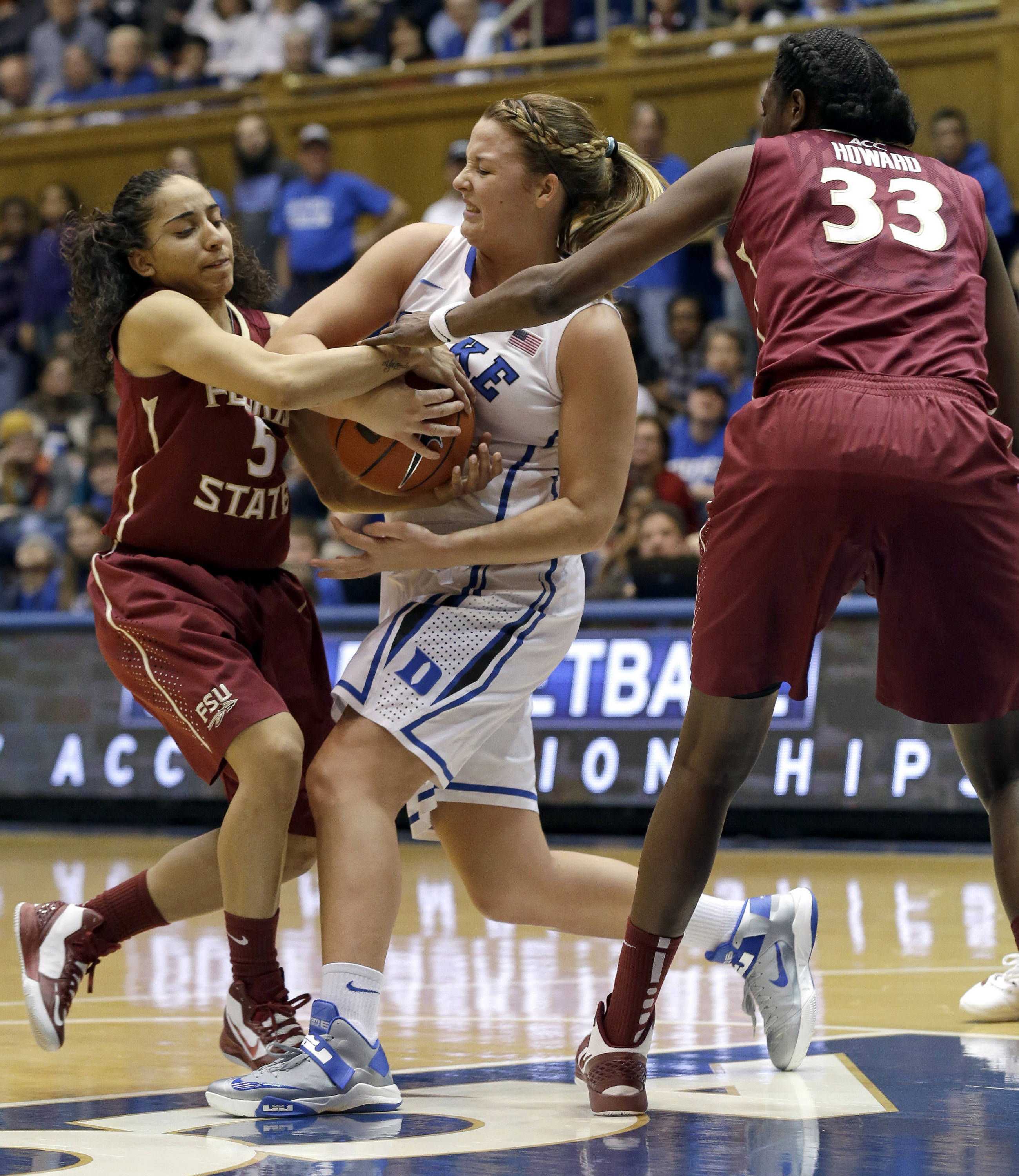 Duke's Tricia Liston, center, struggles for possession of the ball with Florida State's Yashira Delgado (5) and Natasha Howard (33). (AP Photo/Gerry Broome)
