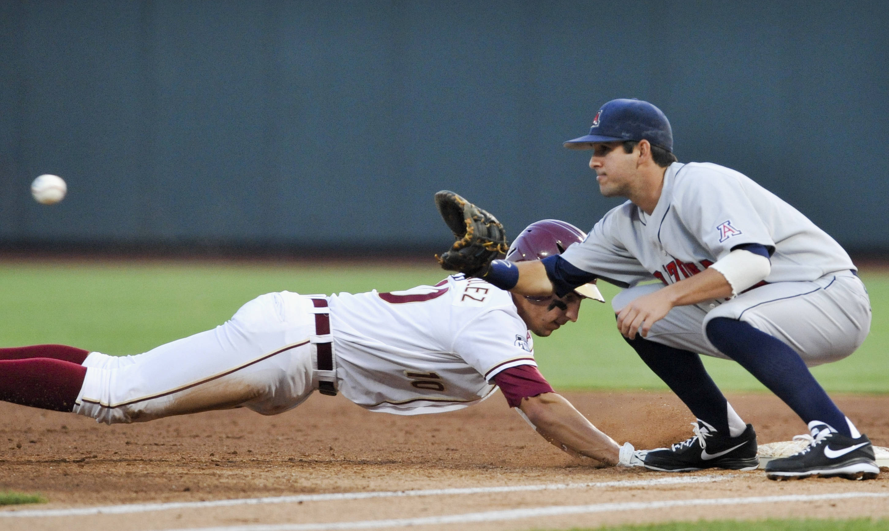 Florida State's Justin Gonzalez returns safely to first as Arizona first baseman Joseph Maggi awaits the pick-off throw in the second inning. (AP Photo/Dave Weaver)