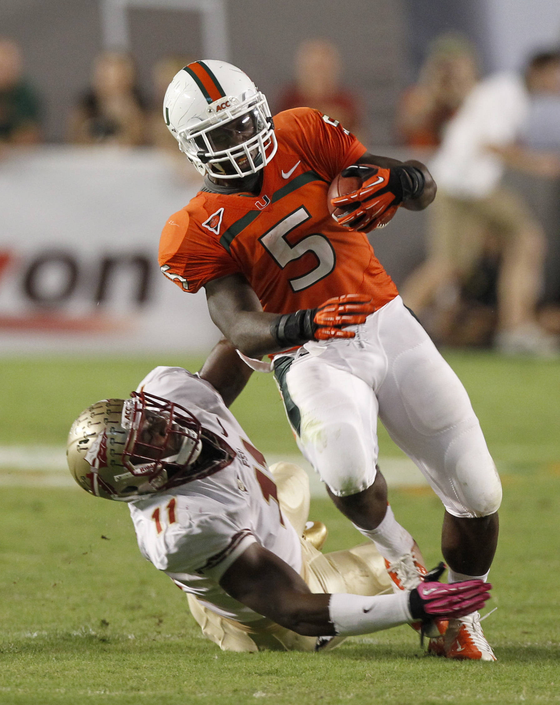 Miami's Mike James (5) is brought down by Florida State's linebacker Vince Williams (11) during the half of an NCAA college football game in Miami, Saturday, Oct. 20, 2012. (AP Photo/Alan Diaz)