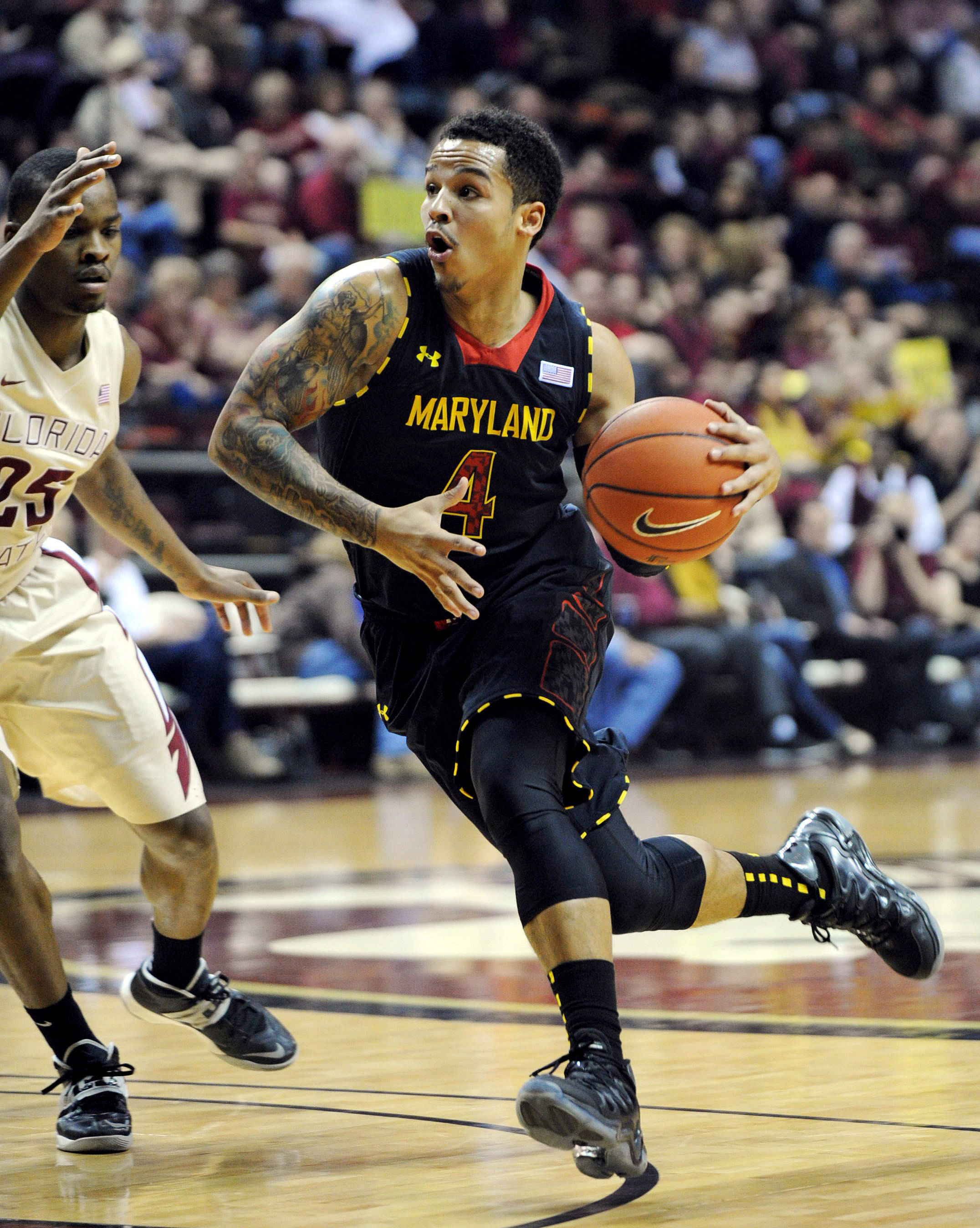 Jan 12, 2014; Tallahassee, FL, USA; Maryland Terrapins guard Seth Allen (4) moves the ball past Florida State Seminoles guard Aaron Thomas (25) during the first half of the game at the Donald L. Tucker Center. Mandatory Credit: Melina Vastola-USA TODAY Sports