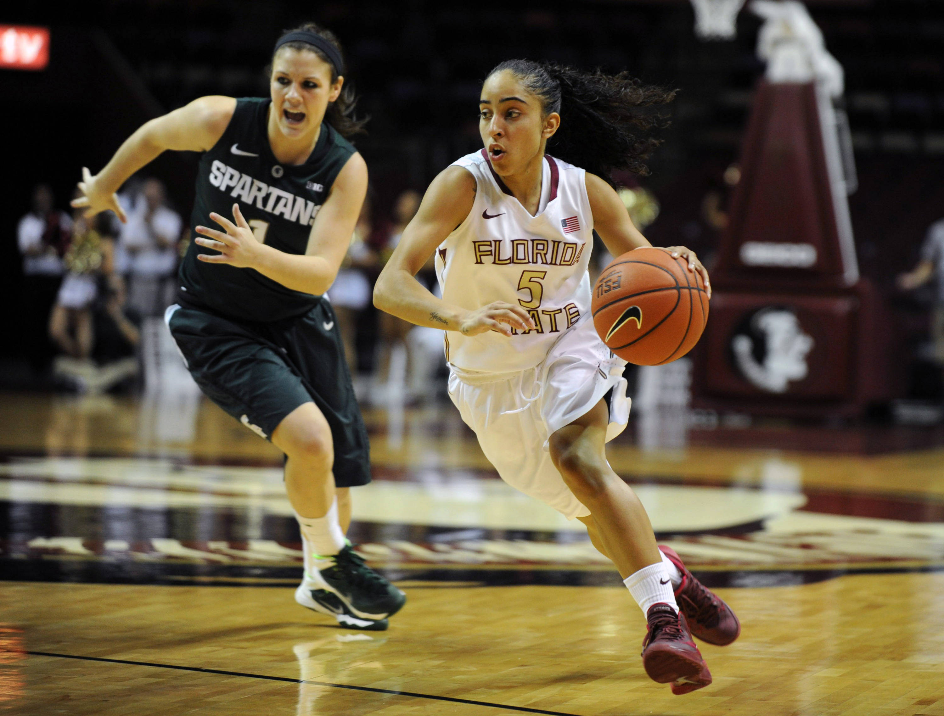 Dec 4, 2013; Tallahassee, FL, USA; Florida State Seminoles guard Cheetah Delgado (5) moves past Michigan State Spartans guard Tori Jankoska (1) during the game at the Donald L. Tucker Center. Mandatory Credit: Melina Vastola-USA TODAY Sports
