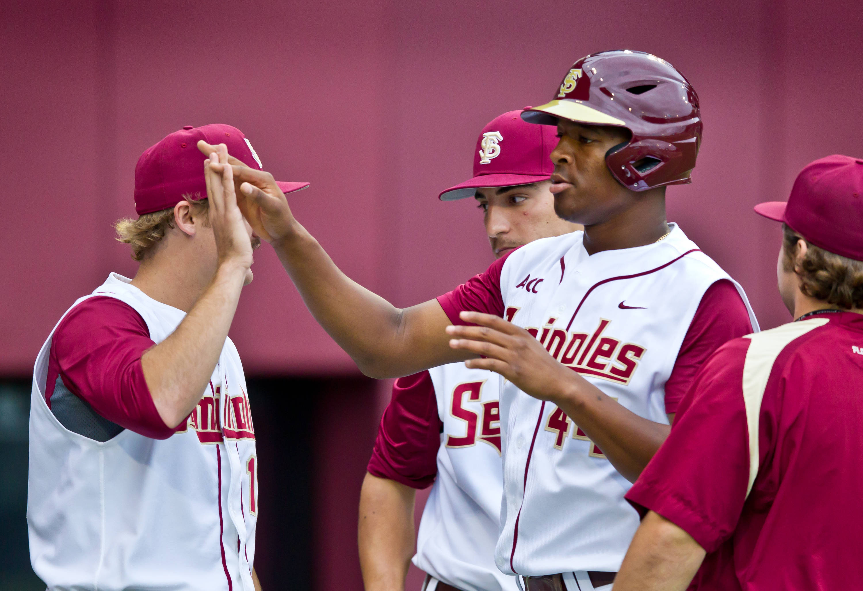 Jameis Winston is greeted at home after scoring the first run of the game.