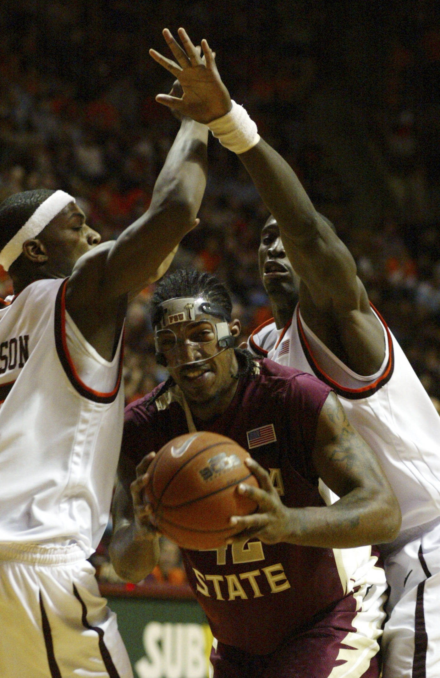 Florida State's Ryan Reid, center, gets past Virginia Tech's J.T. Thompson, left, and Cheick Diakite, right, during the first half of a college basketball game in Blacksburg, Va., Tuesday, Jan. 29, 2008.