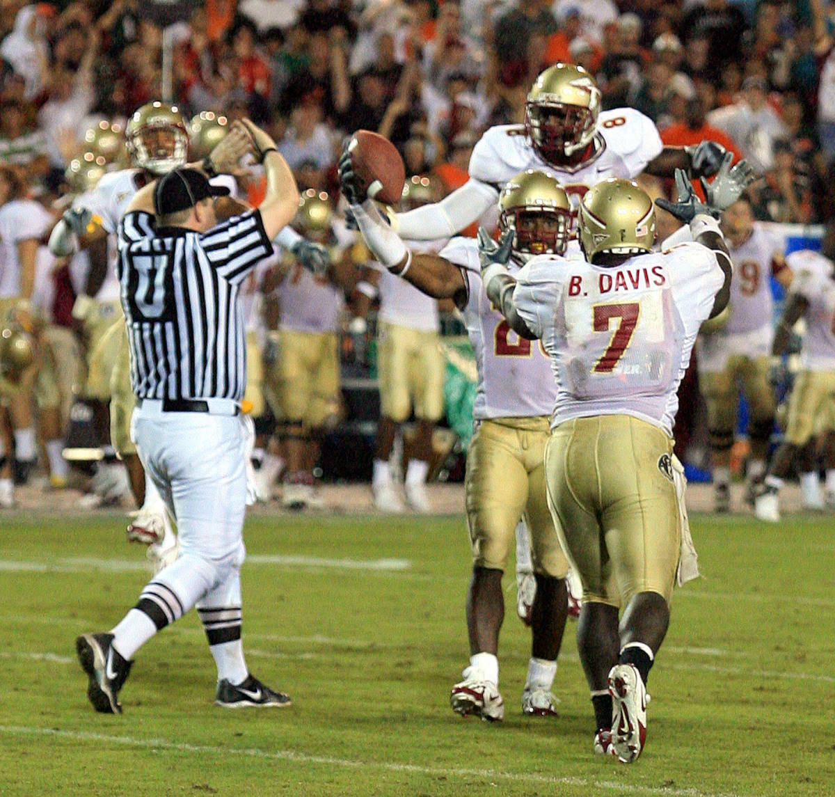 Florida State defensive back Michael Ray Garvin, center right, celebrates with linebacker Buster Davis (7) and safety Roger Williams after Garvin intercepted Miami quarterback Kyle Wright's final pass with 29 seconds left in the fourth quarter of footballMonday, Sept. 4, 2006 at the Orange Bowl in Miami. Florida State defeated Miami 13-10. (AP Photo/Luis M. Alvarez)