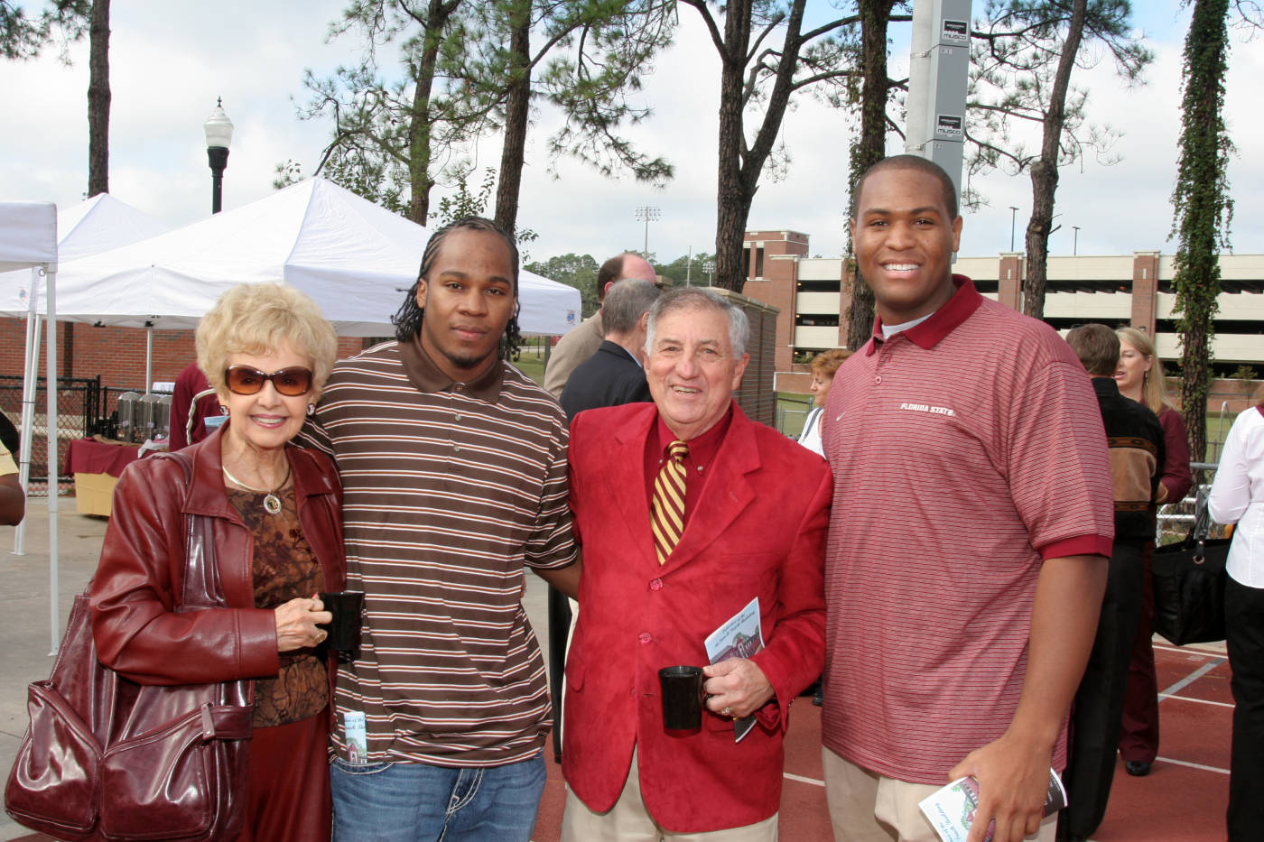Olympian Walter Dix (left) and National Champion Garrett Johnson (right) with two donors.