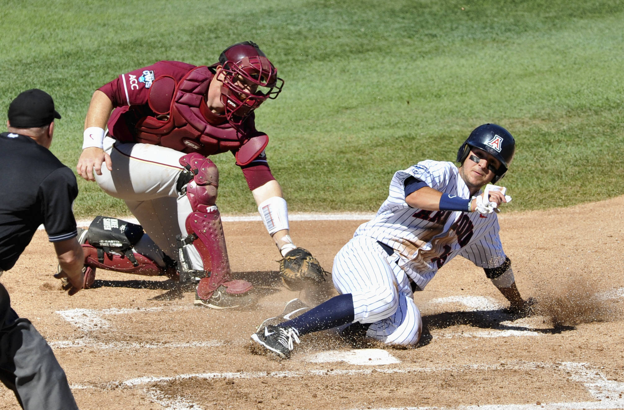 Florida State catcher Stephen McGee is unable to tag out Arizona's Joseph Maggi, right, as he scores on a single hit by Trent Gilbert in the first inning. (AP Photo/Dave Weaver)