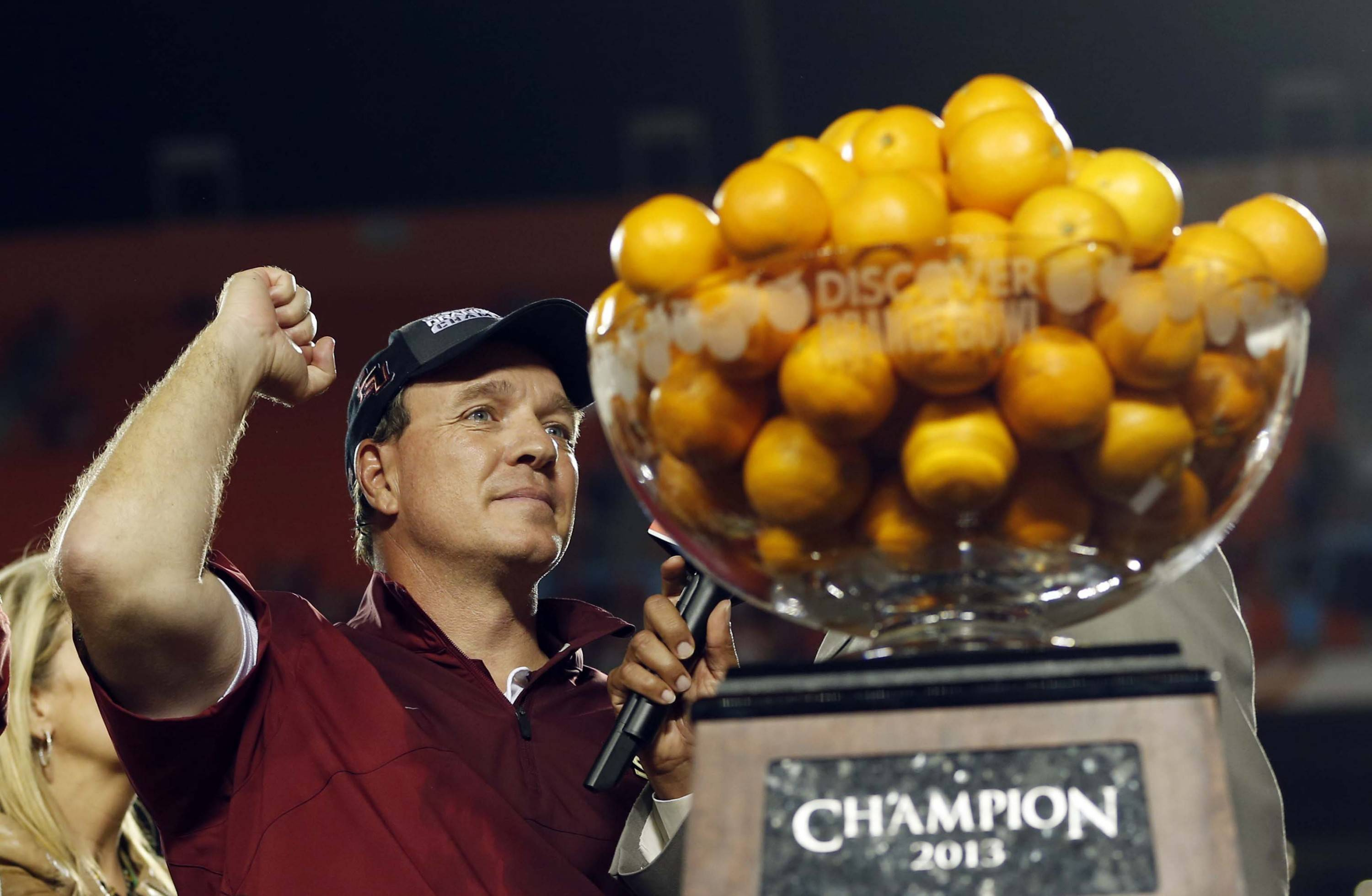 Florida State head coach Jimbo Fisher celebrates next to the Orange Bowl trophy  after defeating Northern Illinois 31-10 at the Orange Bowl NCAA college football game, early Wednesday, Jan. 2, 2013, in Miami. (AP Photo/Alan Diaz)