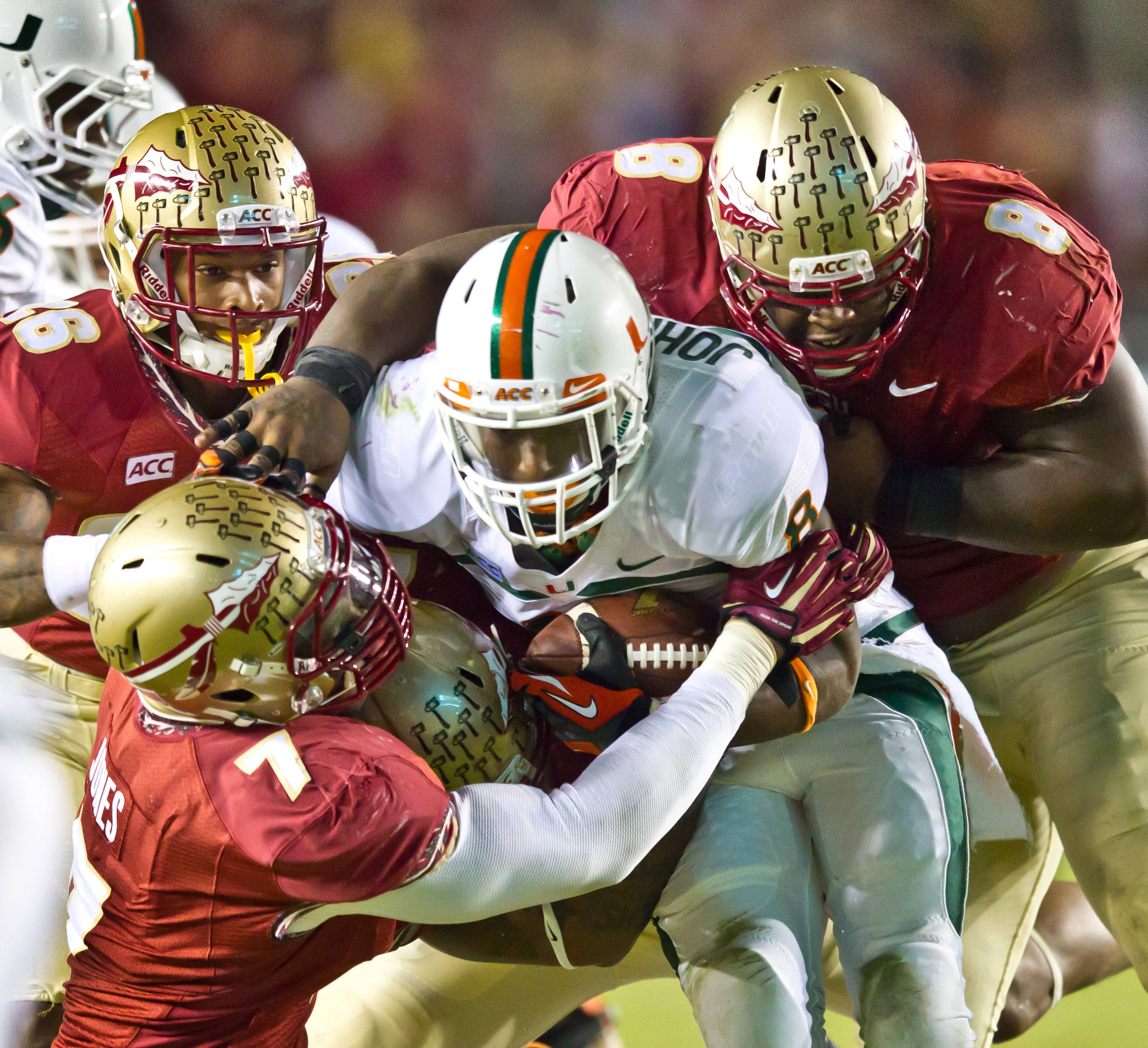 P.J. Williams (26), Christian Jones (7)and Timmy Jernigan (8) stop UM's Duke Johnson.