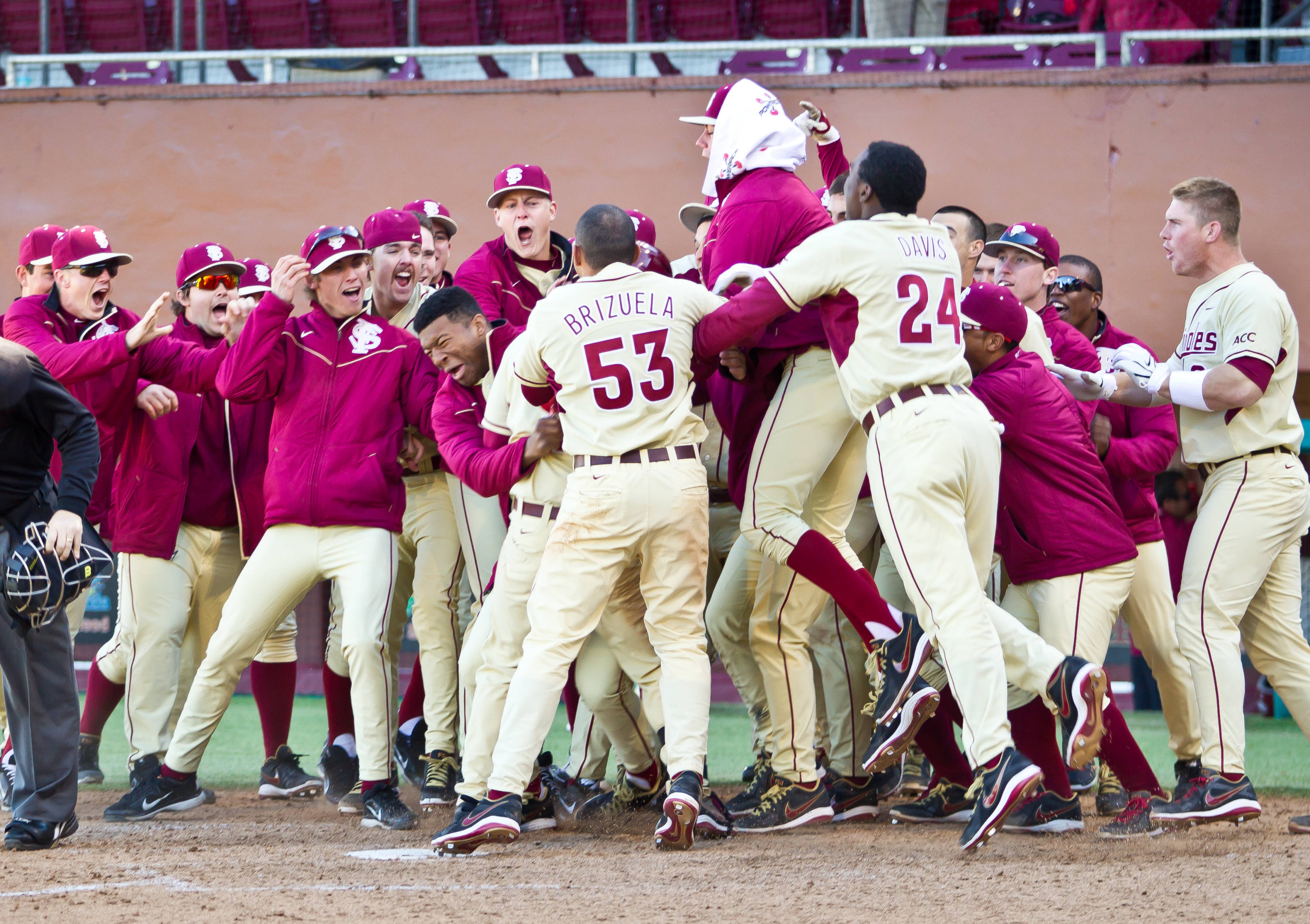 The Seminoles celebrate at the plate with DJ Stewart after the freshman hit a two-run walk-off home run in the 10th inning.