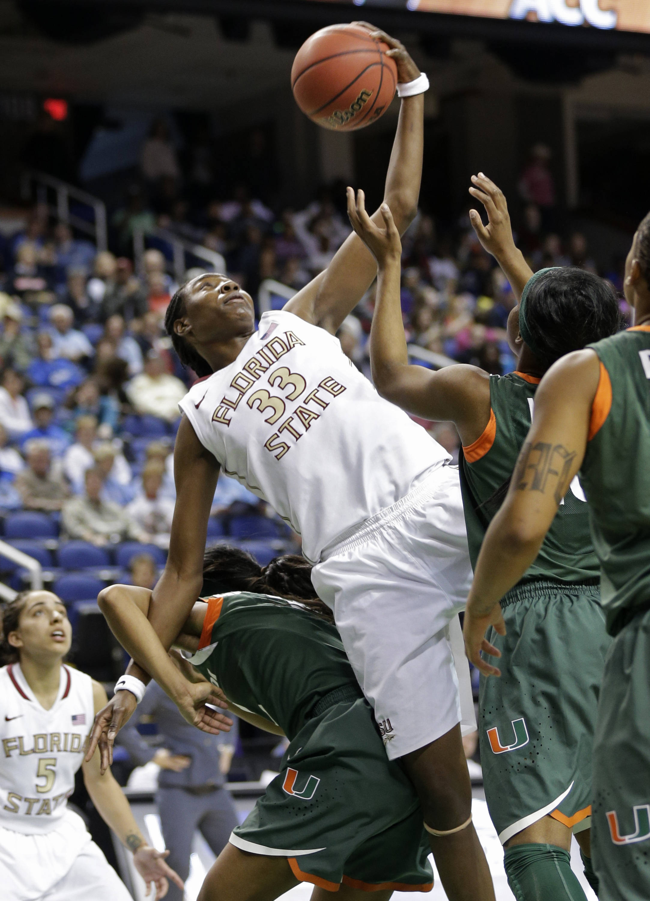 Florida State's Natasha Howard, center, grabs a rebound over Miami's Krystal Saunders, left, and Michelle Woods. (AP Photo/Chuck Burton)
