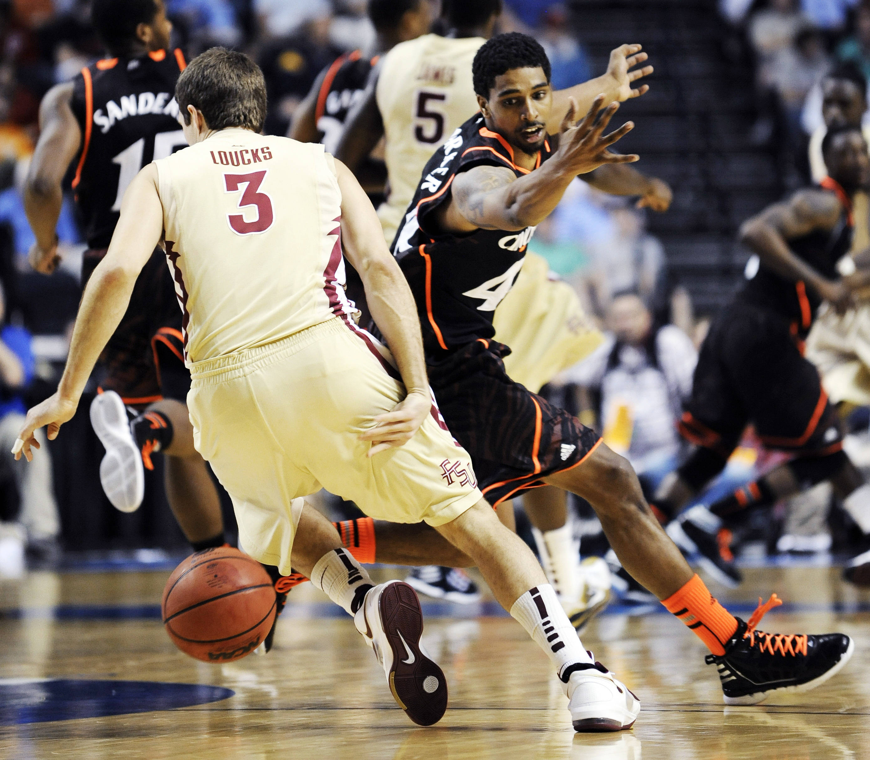 Florida State guard Luke Loucks (3) dribbles behind his back to get past Cincinnati guard Jaquon Parker (44). (AP Photo/Donn Jones)