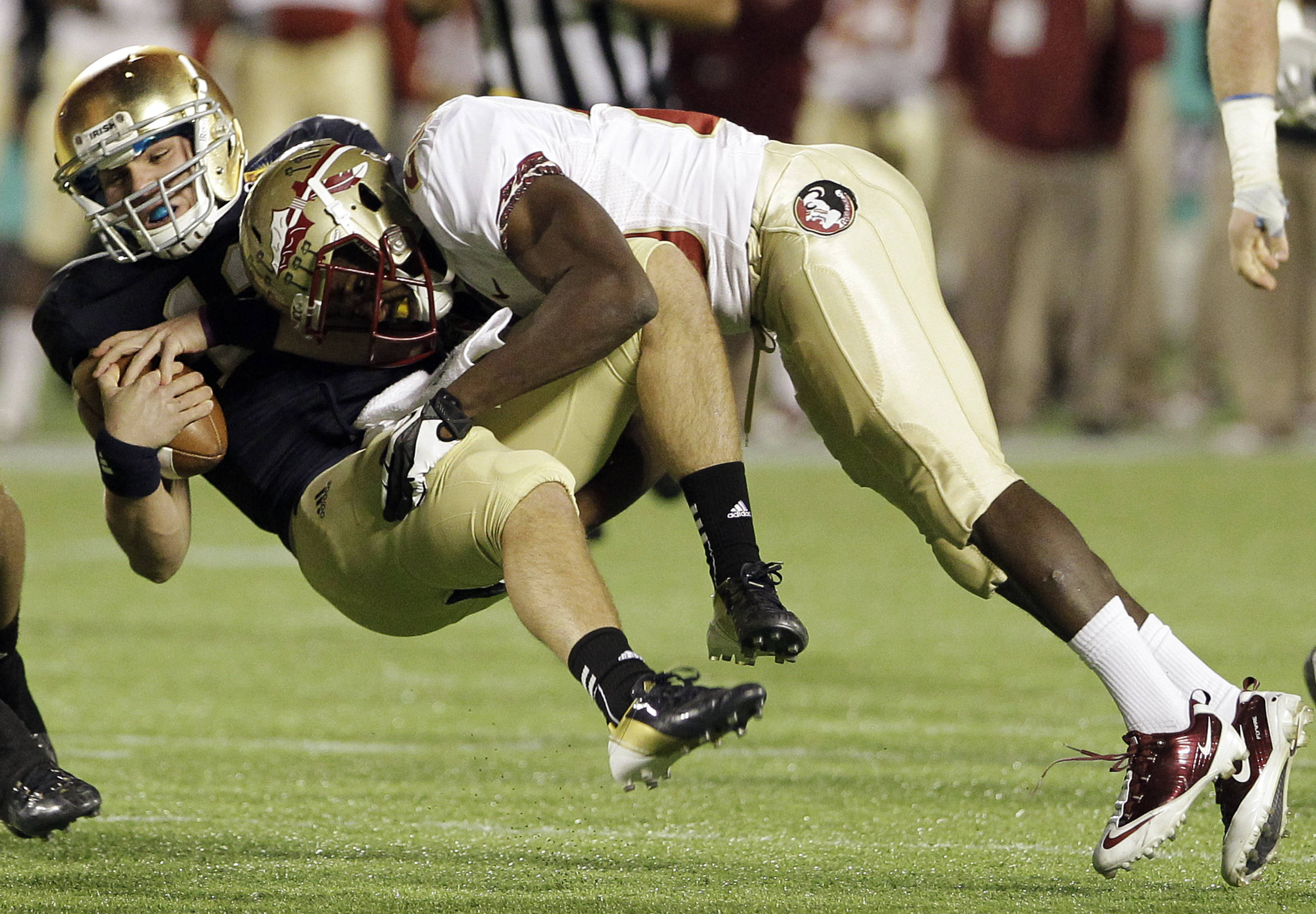 Notre Dame quarterback Tommy Rees, left, is stopped after a short gain by Florida State safety Lamarcus Joyner during the first half. (AP Photo/John Raoux)