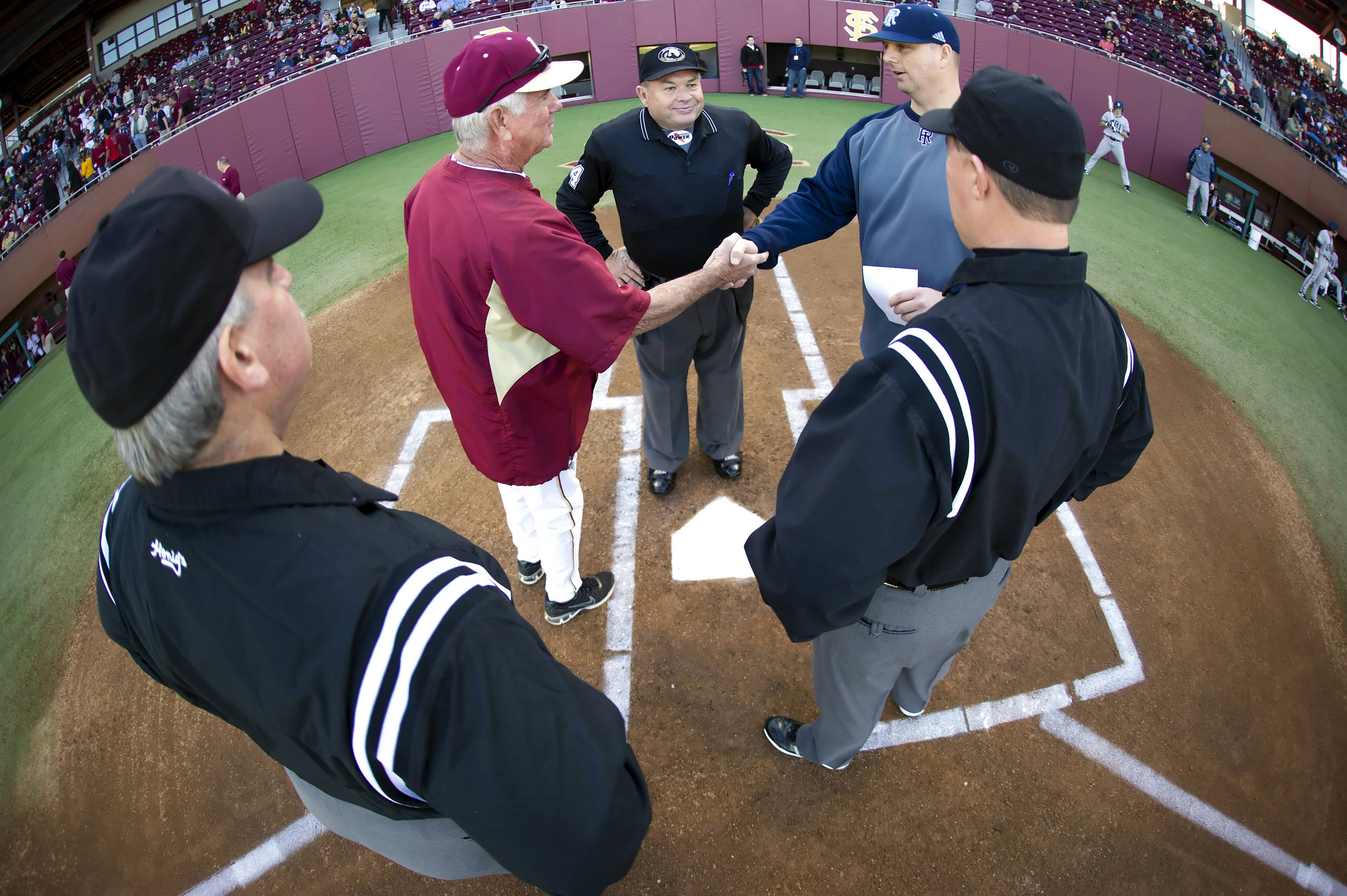 FSU head coach Mike Martin greets URI head coach Jim Foster at home plate before the start of Friday's season opener.