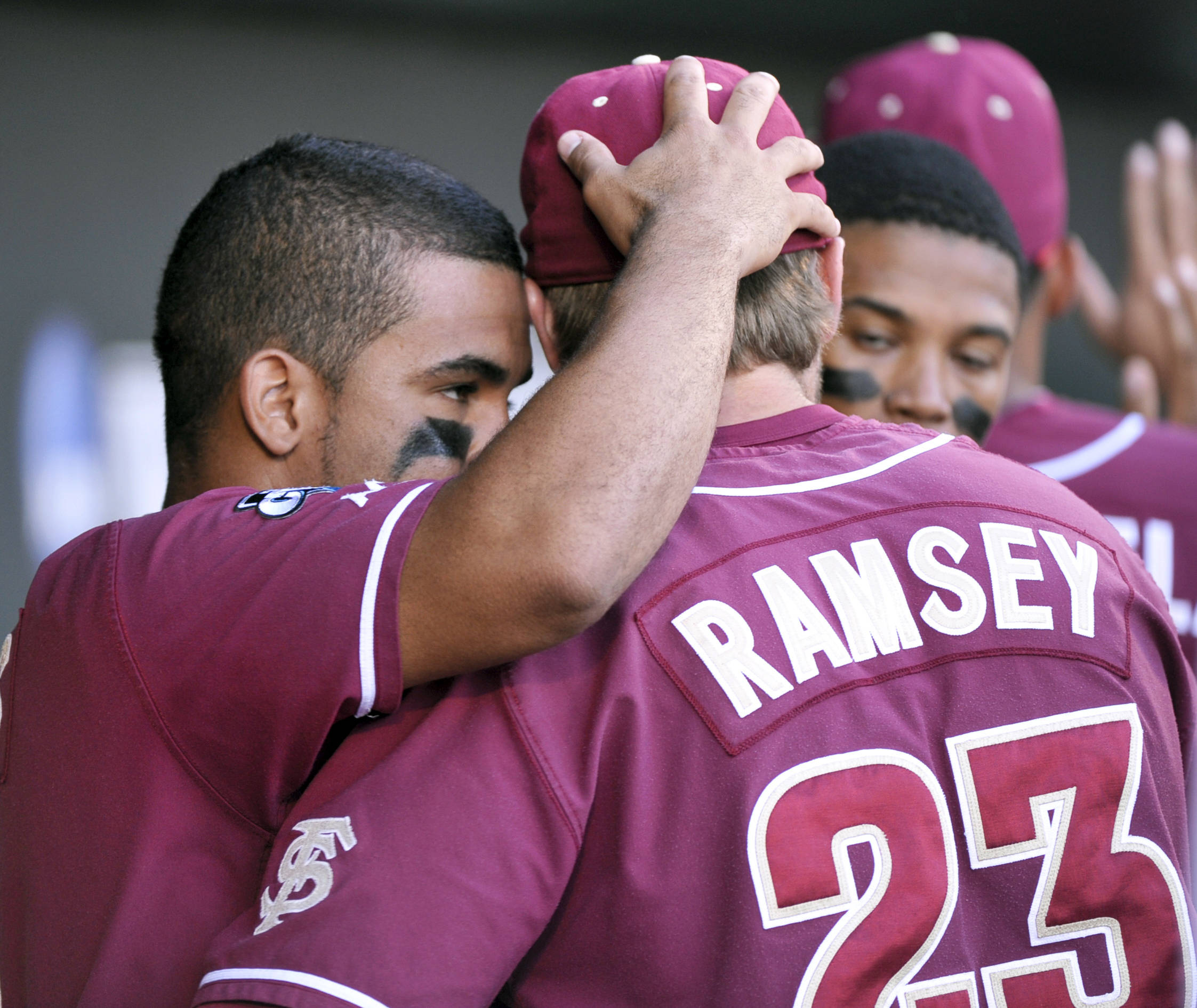 Florida State's Devon Travis, left, and James Ramsey hug in the dugout during the ninth inning. (AP Photo/Ted Kirk)