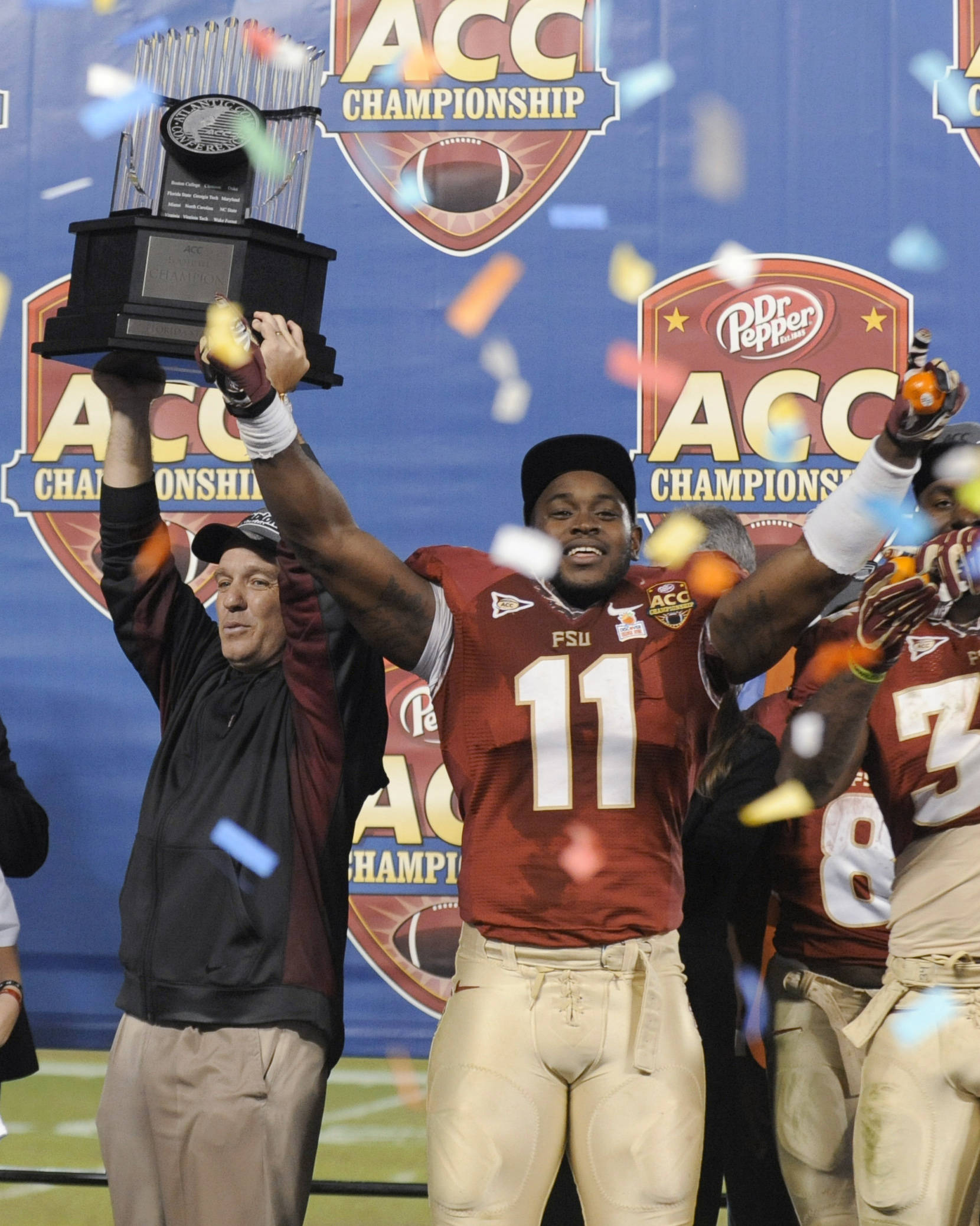 Florida State coach Jimbo Fisher, left, raises the trophy as Vince Williams (11) celebrates following the team's 21-15 win over Georgia Tech in the ACC championship. (AP Photo/Mike McCarn)