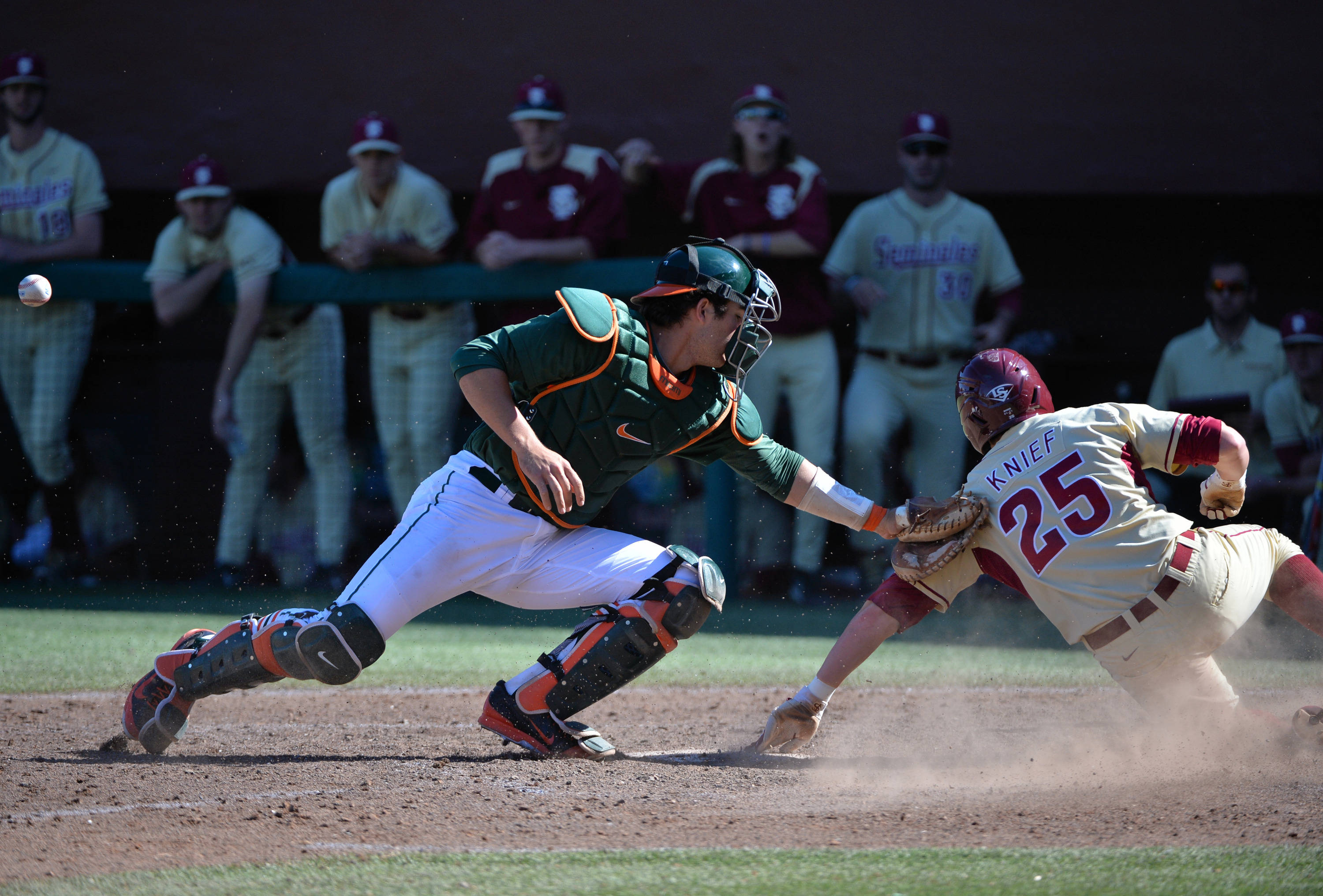 Brett Knief slides a head of the tag at home plate.
