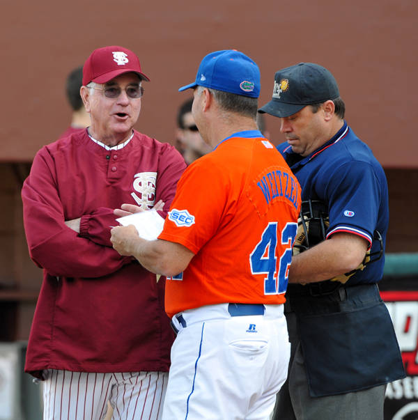 FSU head coach Mike Martin and UF assistant coach Brad Weitzel exchange line-ups for the start of Tuesday's game.