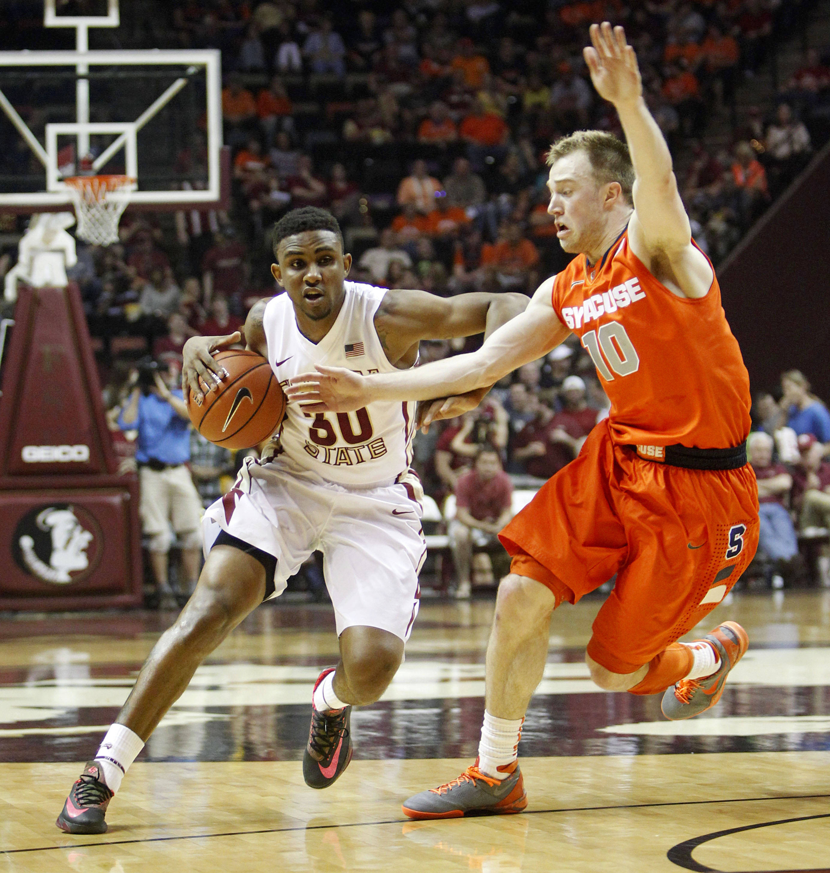 Mar 9, 2014; Tallahassee, FL, USA;  Florida State Seminoles guard Ian Miller (30) drives around Syracuse Orange guard Trevor Cooney (10) during the first half at Donald L. Tucker Center. Mandatory Credit: Matt Stamey-USA TODAY Sports