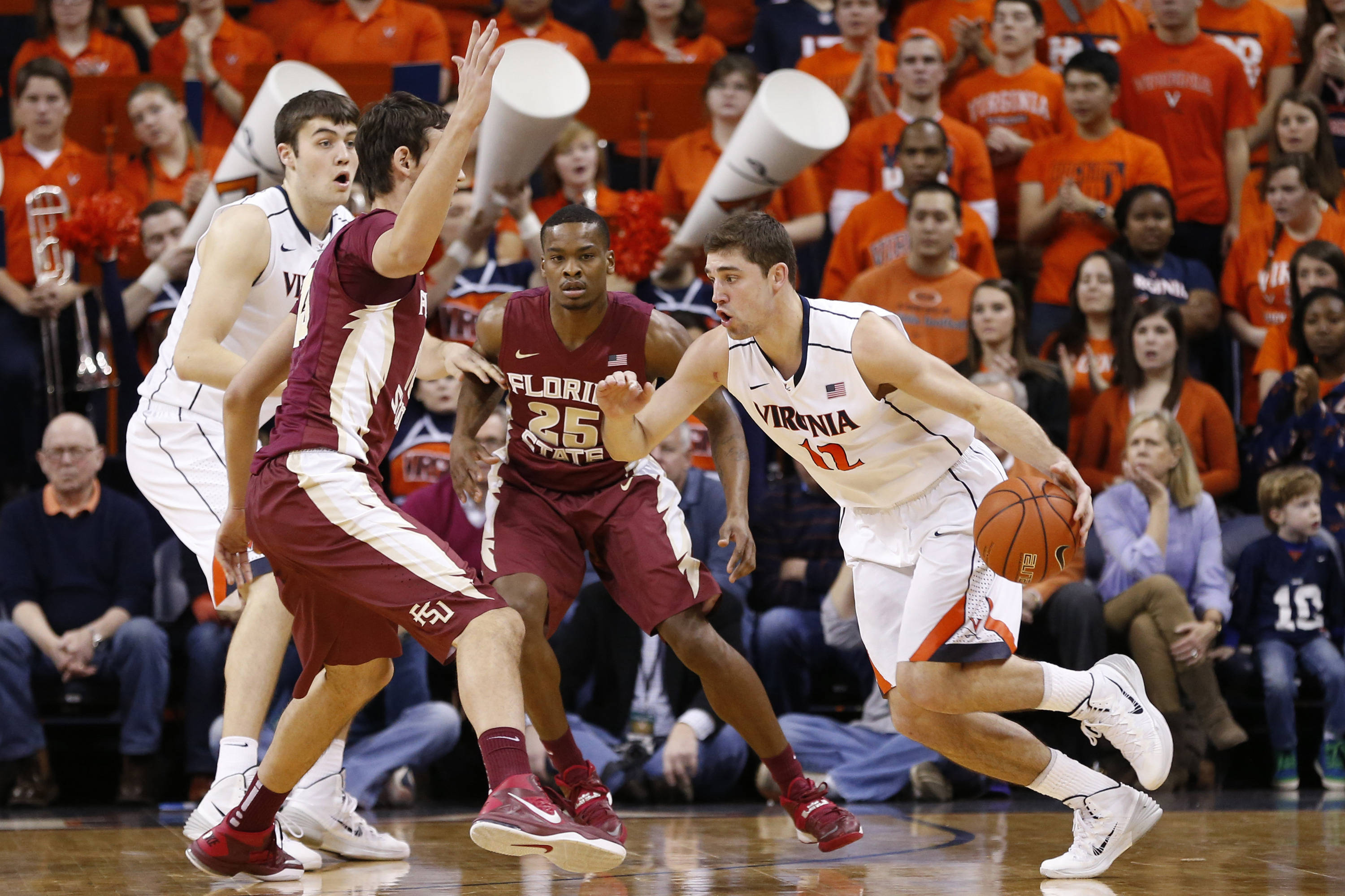 Jan 18, 2014; Charlottesville, VA, USA; Virginia Cavaliers guard Joe Harris (12) dribbles the ball around Florida State Seminoles center Boris Bojanovsky (15) and Seminoles guard Aaron Thomas (25) in the first half at John Paul Jones Arena. Mandatory Credit: Geoff Burke-USA TODAY Sports