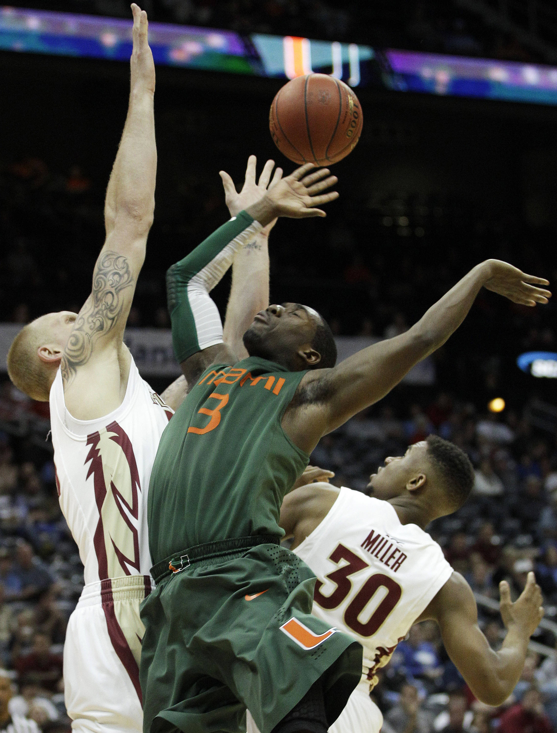 Miami guard Malcolm Grant (3), Florida State center Jon Kreft, left, and Florida State guard Ian Miller (30) vie for a loose ball during the second half of an NCAA college basketball game in the quarterfinals of the Atlantic Coast Conference tournament, Friday, March 9, 2012, in Atlanta. (AP Photo/Chuck Burton)