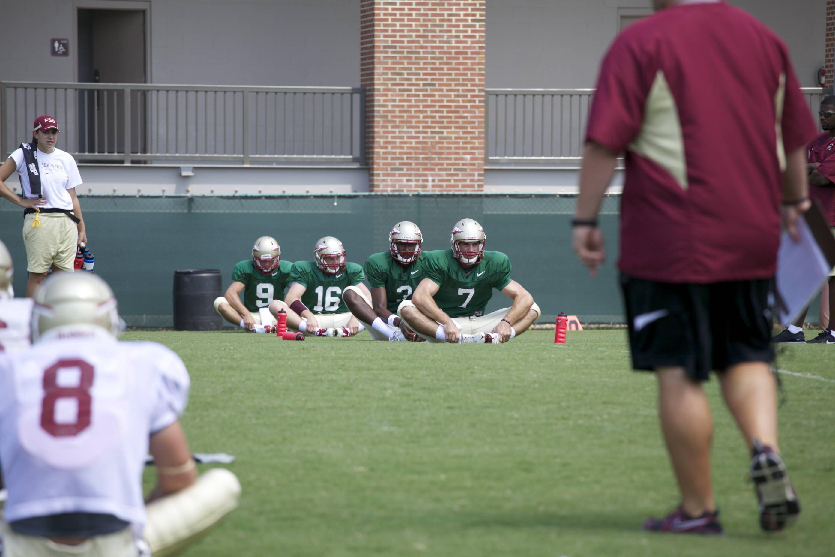 Quarterbacks stretching before practice
