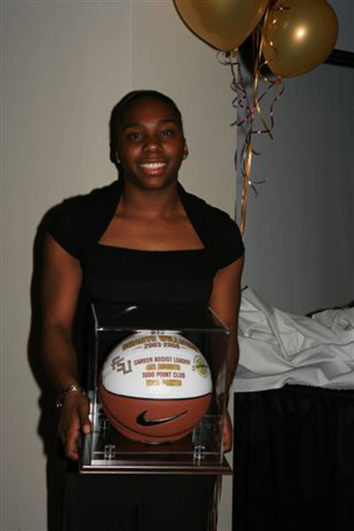 Shante Williams with the game ball for breaking the school's assist record and scoring 1,000 points.