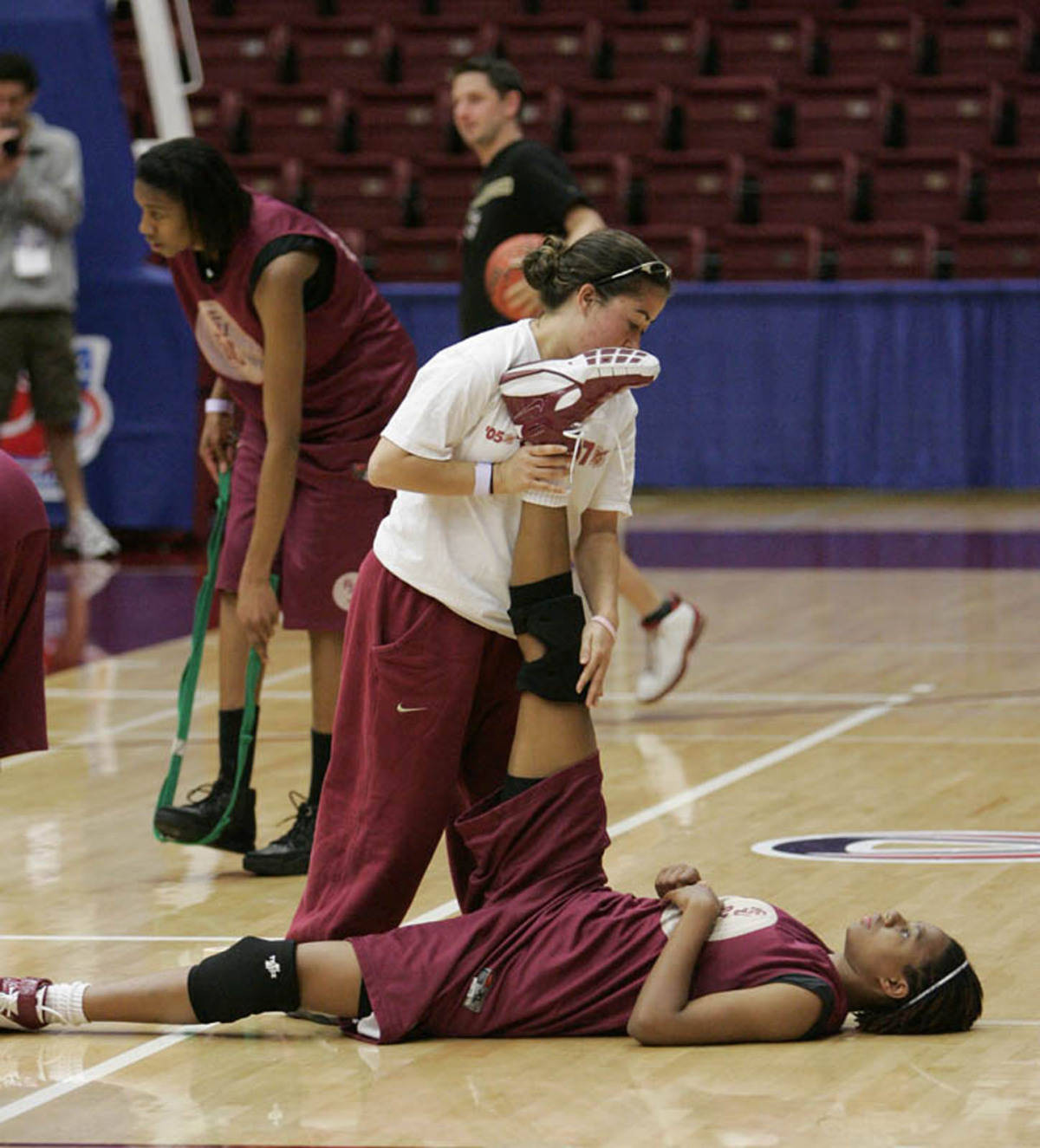 Graduate Assistant Theodora Scott stretch out a player.