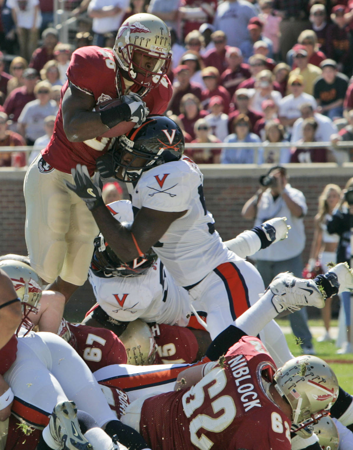 Florida State's Lorenzo Booker scores a first-quarter touchdown over Virginia's Antonio Appleby during a college football game Saturday, Nov. 4, 2006, in Tallahassee, Fla. Booker's touchdown came on the play after the Seminoles blocked a Virginia punt. (AP Photo/Phil Coale)