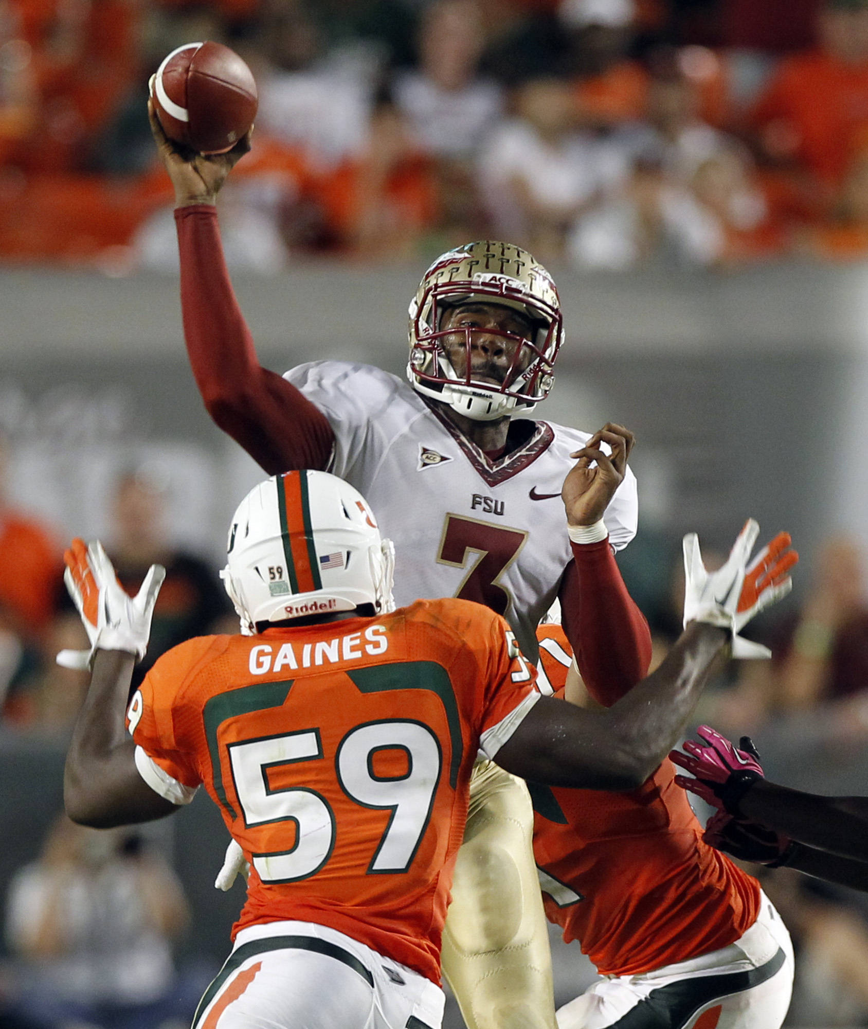 Florida State quarterback EJ Manuel (3) passes over Miami's Jimmy Gaines (59) during the first half of an NCAA college football game in Miami, Saturday, Oct. 20, 2012. (AP Photo/Alan Diaz)
