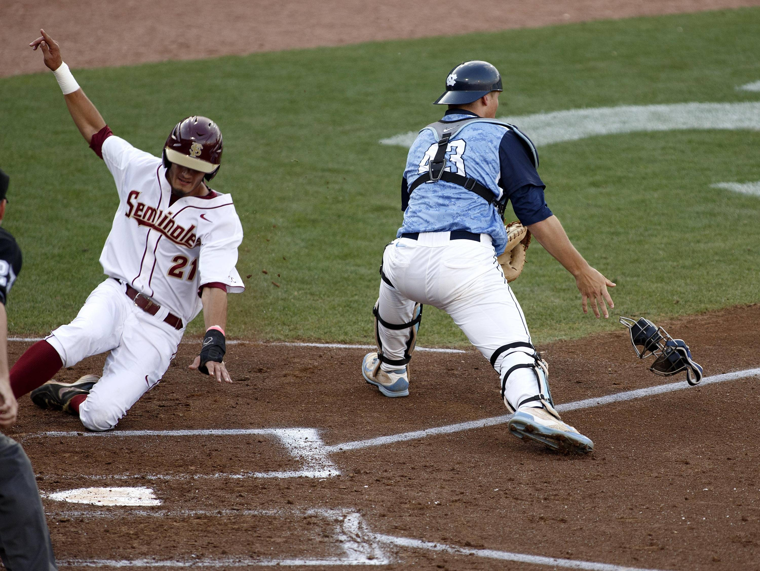 Florida State infielder Ben DeLuzio is safe as North Carolina catcher Korey Dunbar fields the throw.