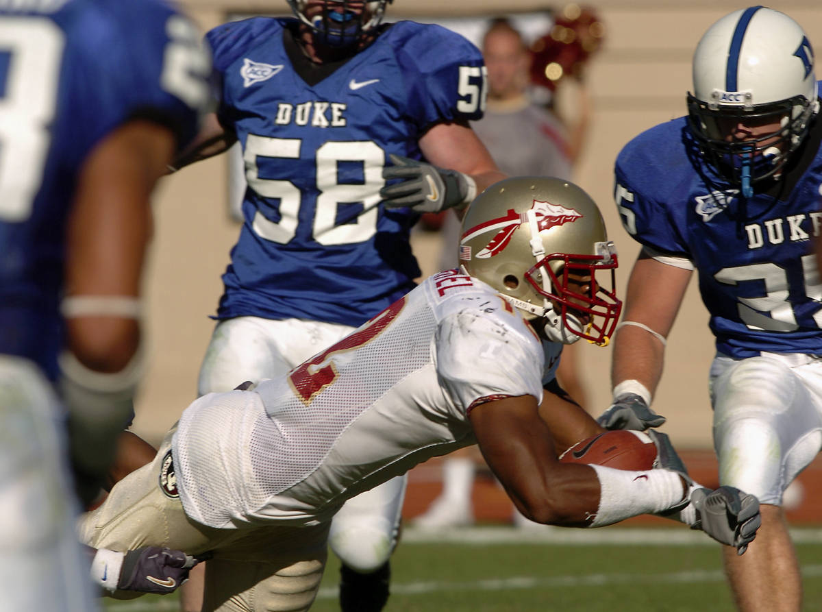 Florida State's Damon McDaniel (12) dives into the end zone for a touchdown in the second half of a college football game in Durham, N.C., Saturday, Oct. 14, 2006. Florida State won 51-24. At rear are Duke's Codey Lowe (58) and Tim Ball (35). (AP Photo/Sara D. Davis)